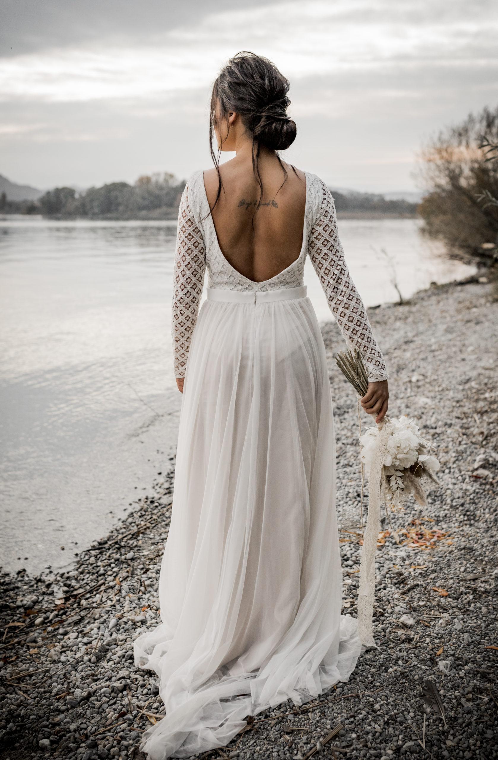 noni Brautmode, Styled Shoot am Bodensee, Model mit zweiteiligem Hochzeitskleid mit tiefem Rückenausschnitt und langem Tüllrock in Ivory mit Blush, Brautstrauss haltend, Rückenansicht