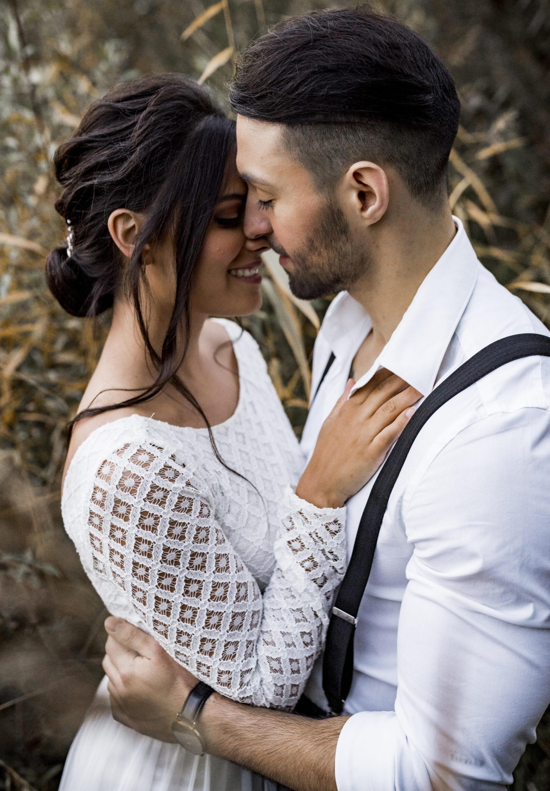 noni Styled Shoot, Model-Paar in Umarmung und lächelnd, Braut mit Oberteil aus weißer, geometrischer Spitze, Bräutigam mit weißem Hemd und Hosenträgern