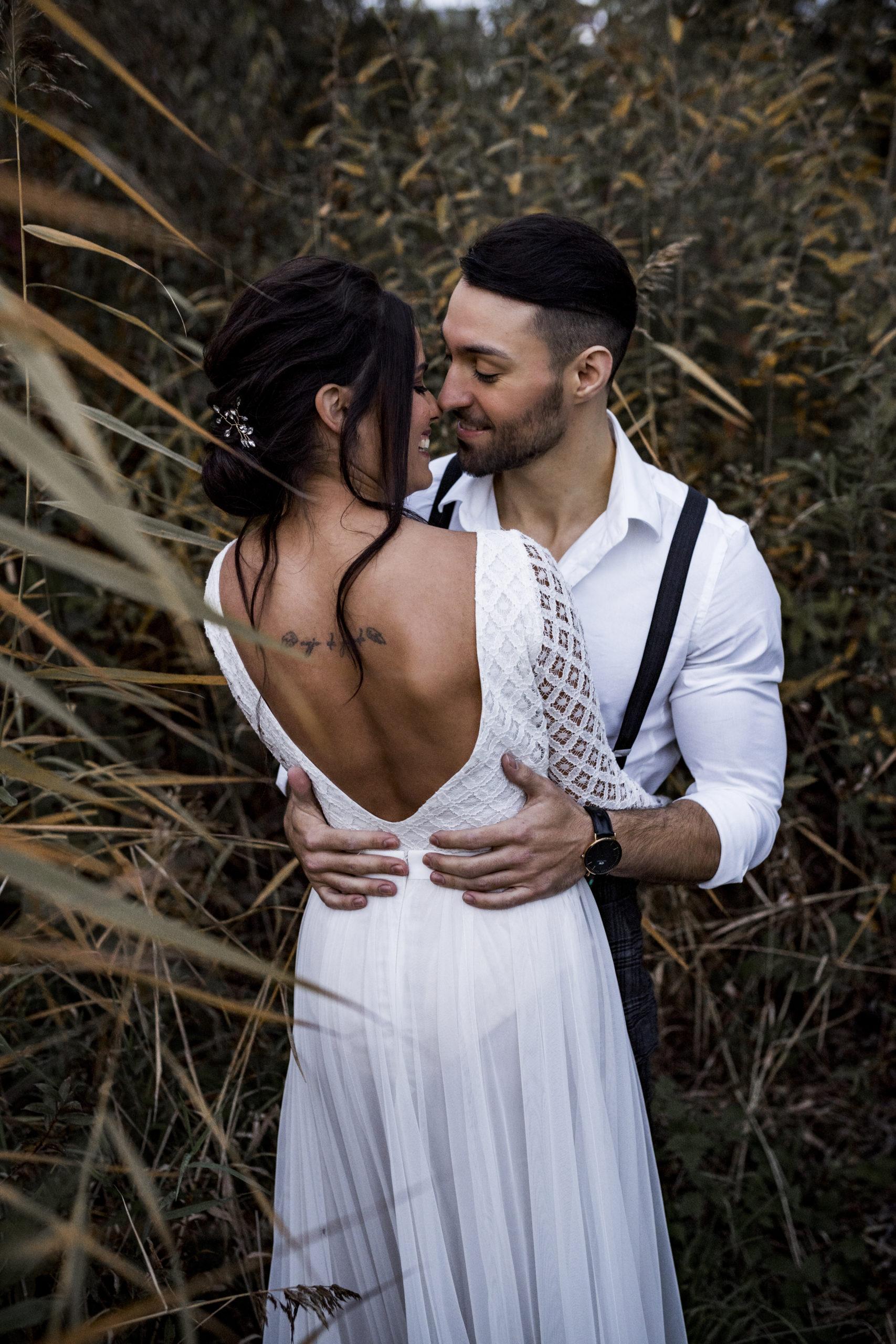 noni Styled Shoot, Model-Paar in Umarmung und lächelnd, Braut mit Oberteil aus weißer, geometrischer Spitze, Bräutigam mit weißem Hemd und Hosenträgern, Rückenansicht