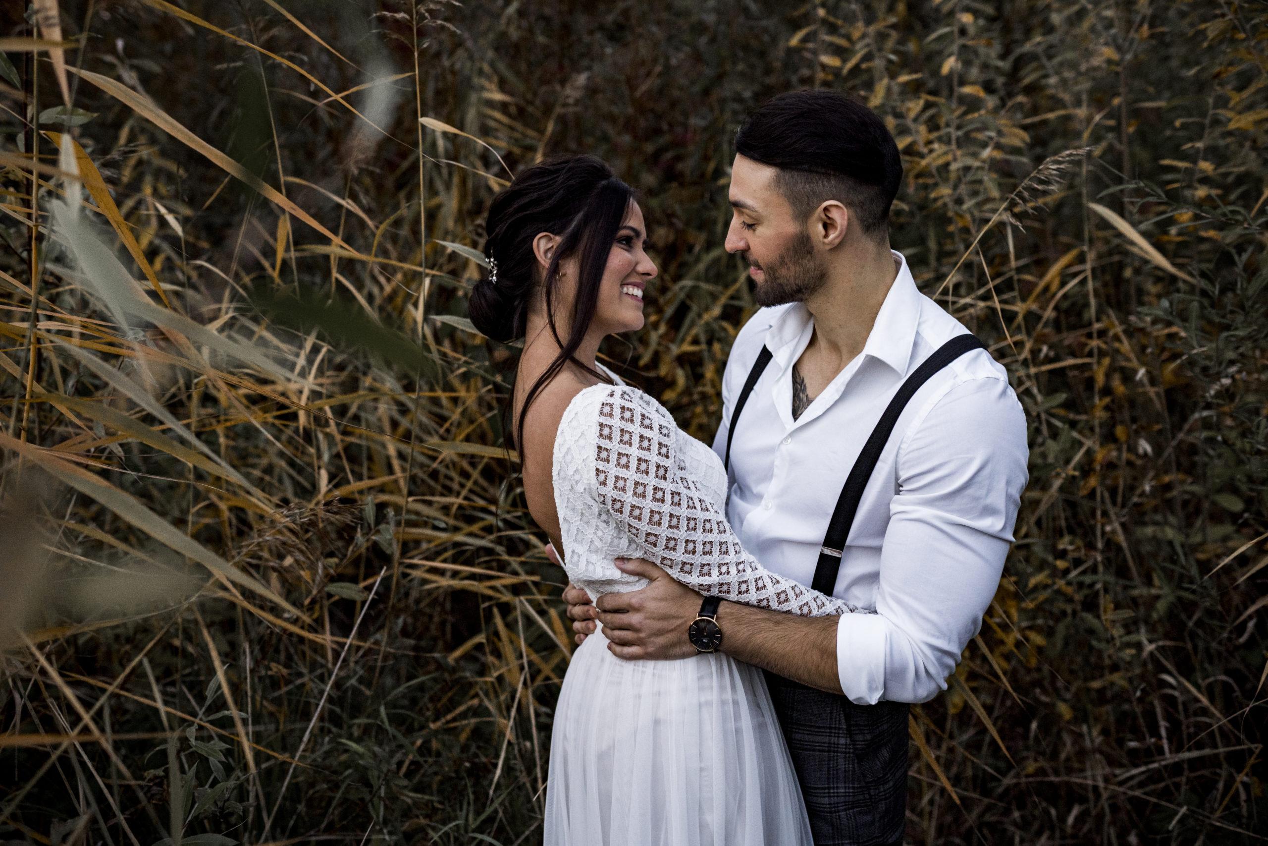 noni Styled Shoot, Model-Paar in Umarmung und lächelnd, Braut mit Oberteil aus weißer, geometrischer Spitze, Bräutigam mit weißem Hemd und Hosenträgern, Seitenansicht