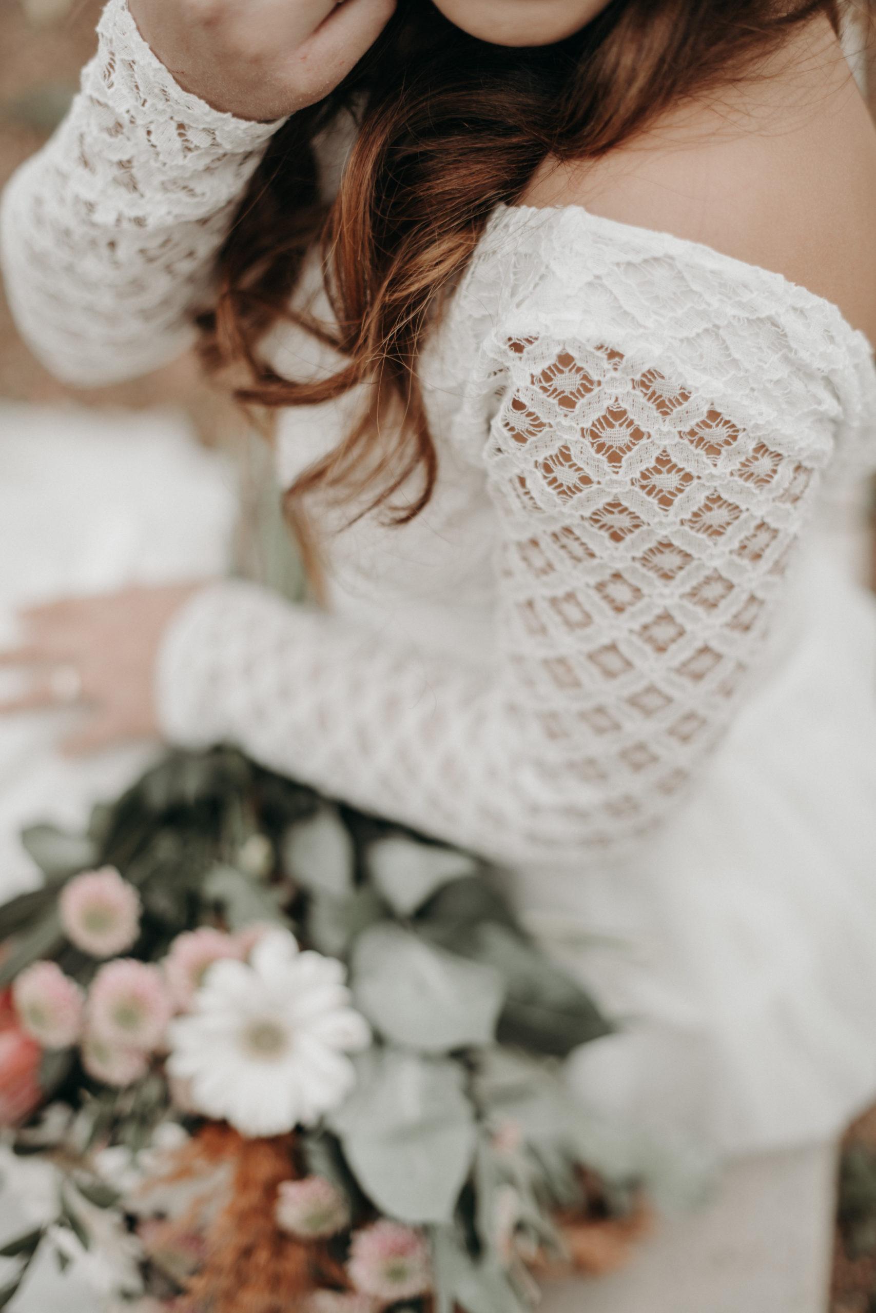 Styled Outdoor-Shoot mit Modelpärchen. Braut mit langärmeligem Top aus geometrischer Spitze und langem weißem Rock, korallenfarbigem Brautstrauss, Nahaufnahme von Strauss und Ärmel