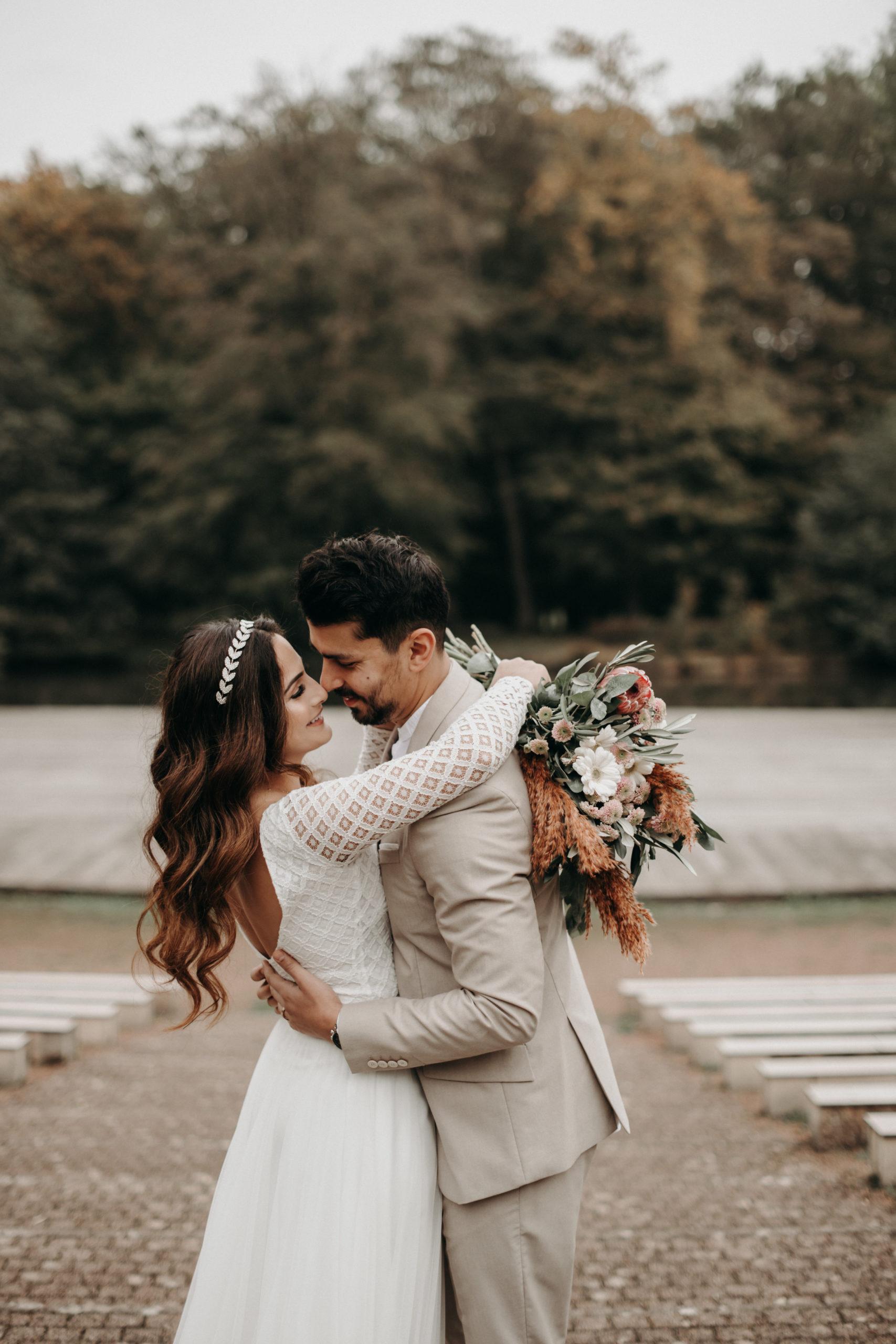 Styled Outdoor-Shoot mit Modelpärchen. Braut mit langärmeligem Top aus geometrischer Spitze und langem weißem Rock, korallenfarbigem Brautstrauss und Tiara. Bräutigam-Model mit hellem Anzug und Henley Shirt