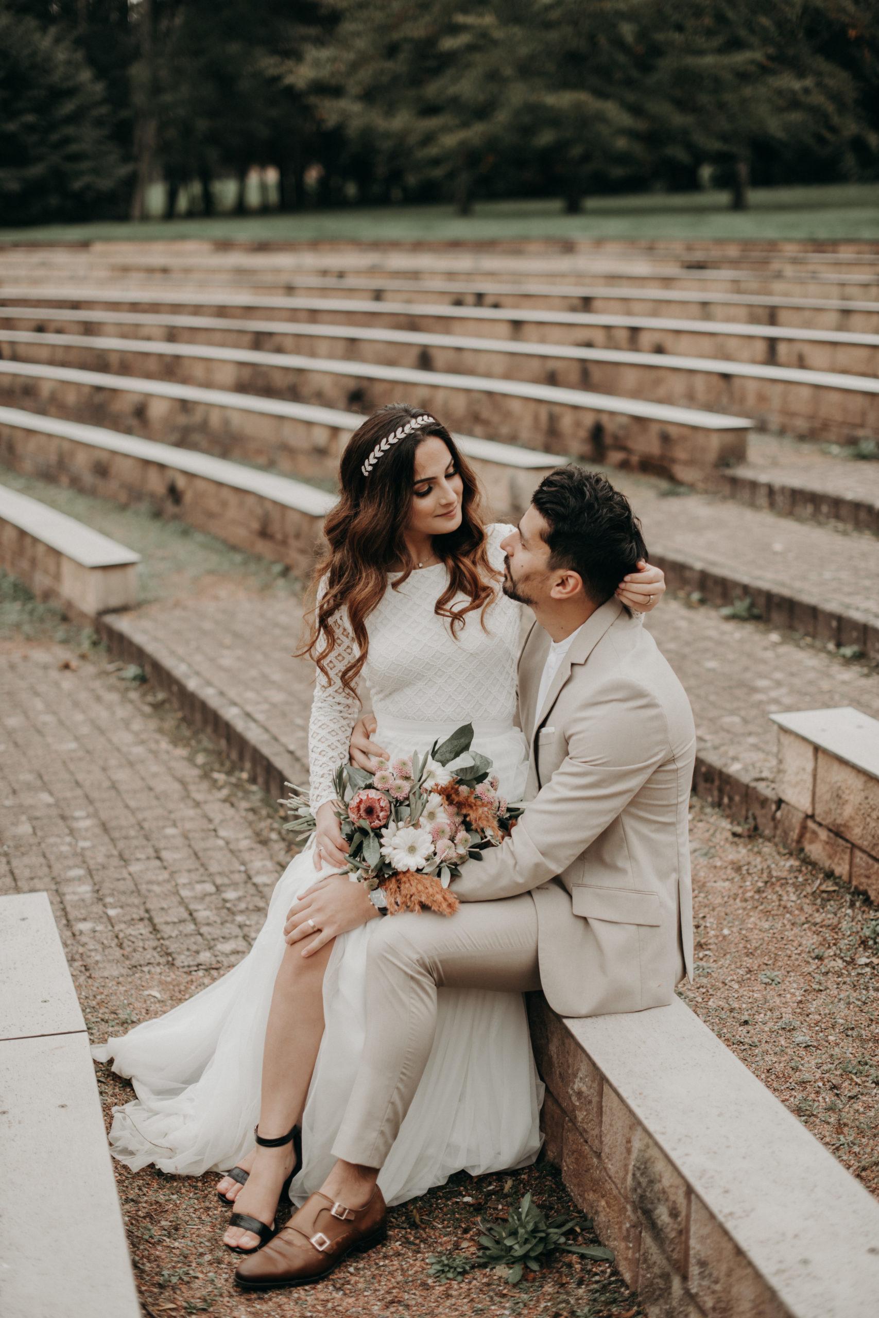 Styled Outdoor-Shoot mit Modelpärchen. Braut mit langärmeligem Top aus geometrischer Spitze und langem weißem Rock, korallenfarbigem Brautstrauss und Tiara. Bräutigam-Model mit hellem Anzug und Henley Shirt, auf Treppe sitzend
