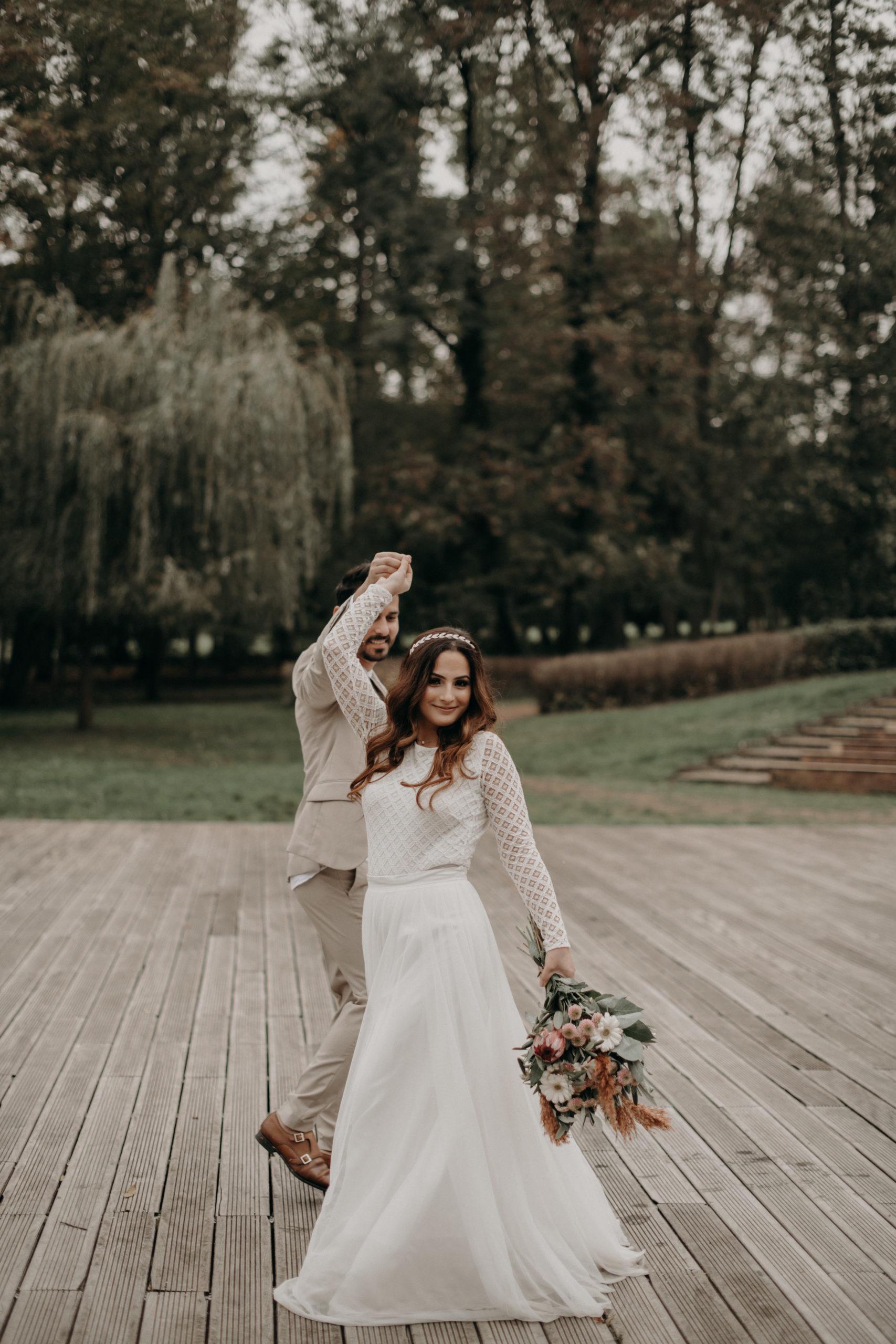 Styled Outdoor-Shoot mit Modelpärchen. Braut mit langärmeligem Top aus geometrischer Spitze und langem weißem Rock, korallenfarbigem Brautstrauss und Tiara. Bräutigam-Model mit hellem Anzug und Henley Shirt, tanzend auf Holz-Veranda