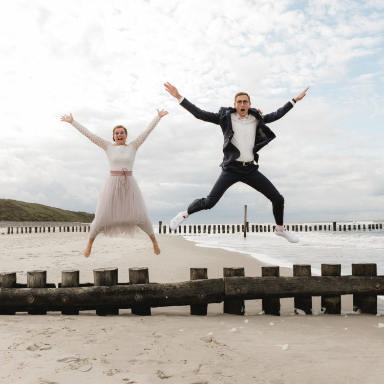 Brautpaar springt in die Luft am Meer