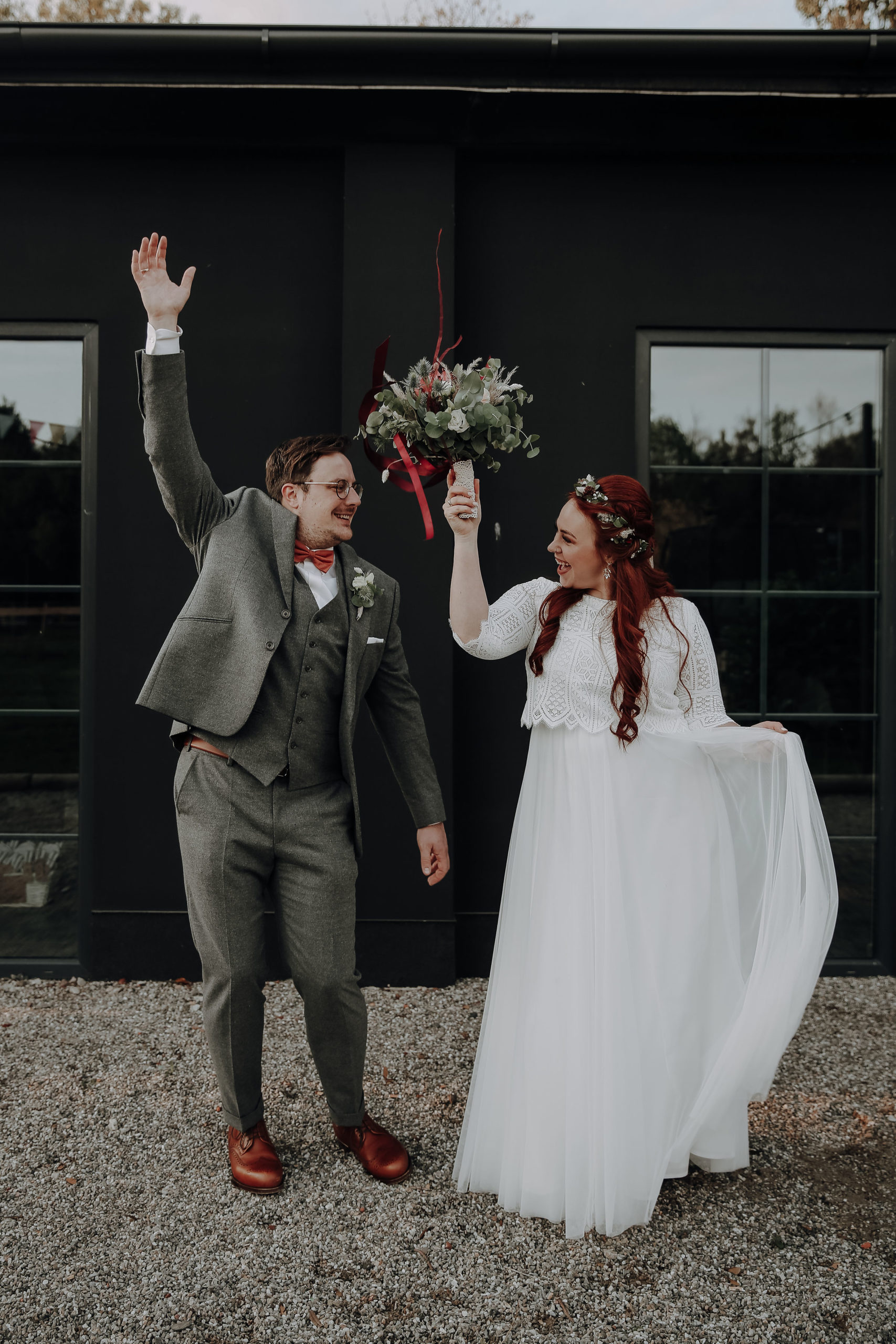 noni Brautmode, Wedding Shoot mit Brautpaar, lachend. Braut mit zweiteiligem Brautkleid im Boho Stil mit Spitzentop und langem Rock, Bräutigam mit grauem Dreiteiler und roter Fliege
