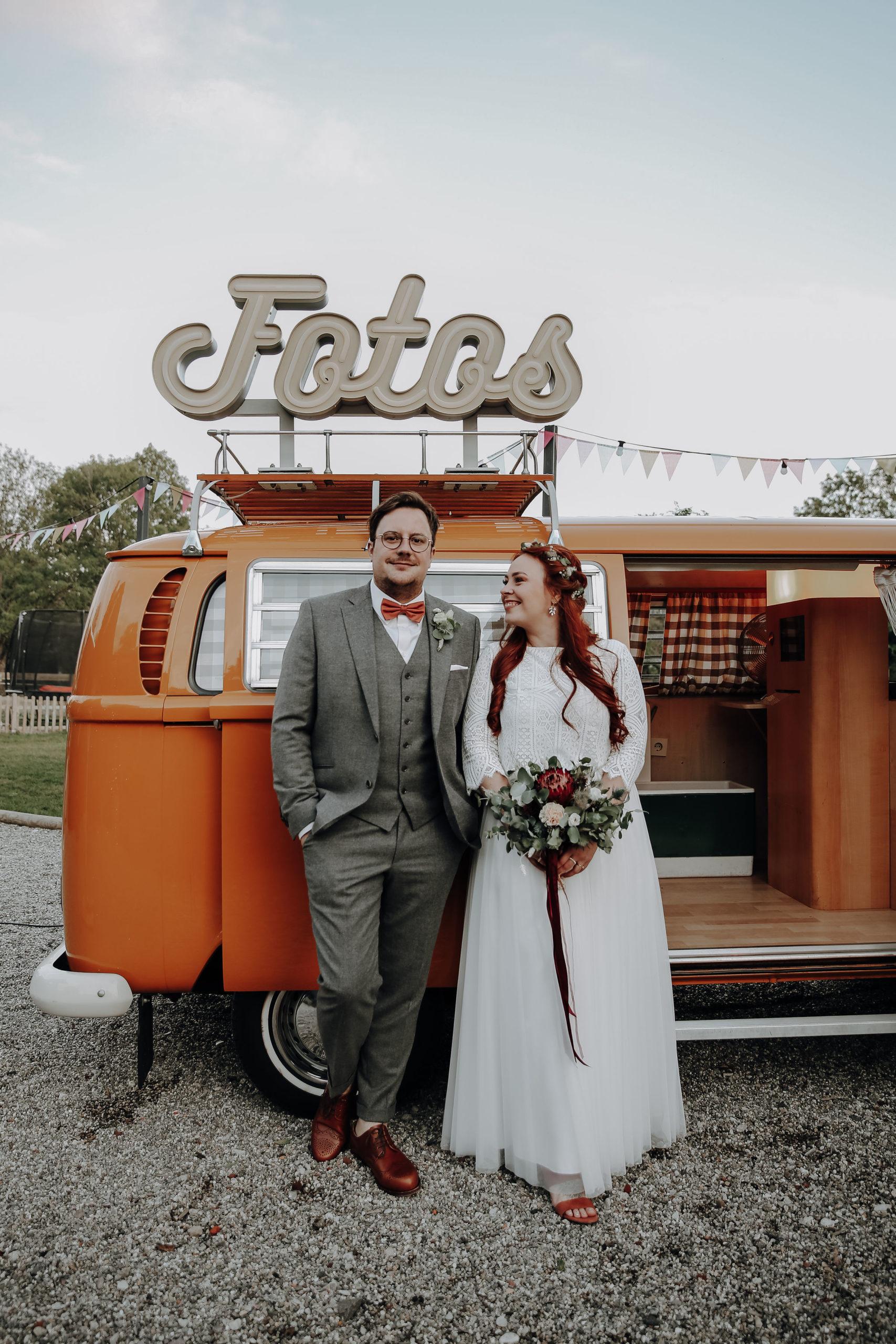 noni Brautmode, Wedding Shoot mit Brautpaar vor rotem Vintage-VW Bus als Fotobooth