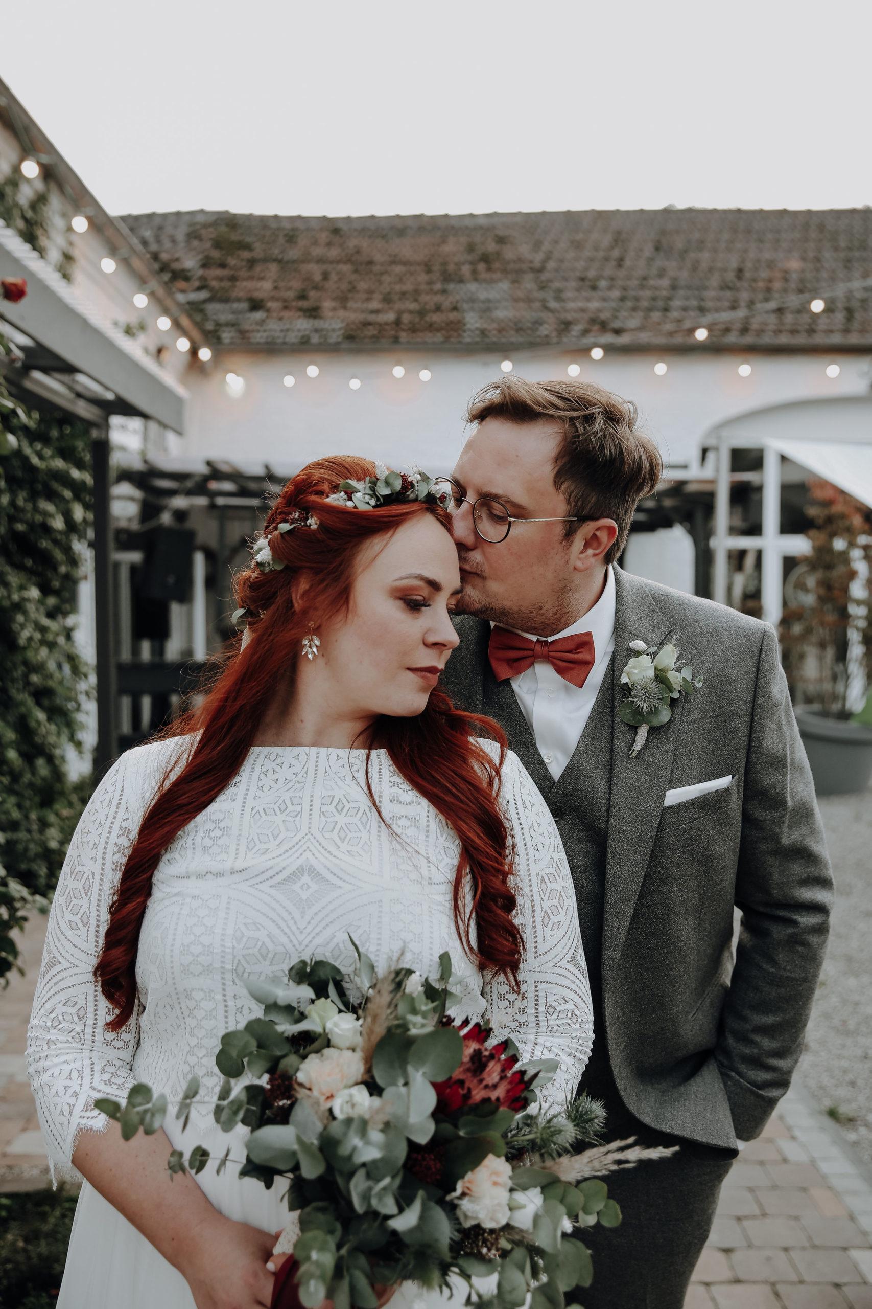 noni Brautmode, Wedding Shoot, Bräutigam küsst Braut auf die Stirn.