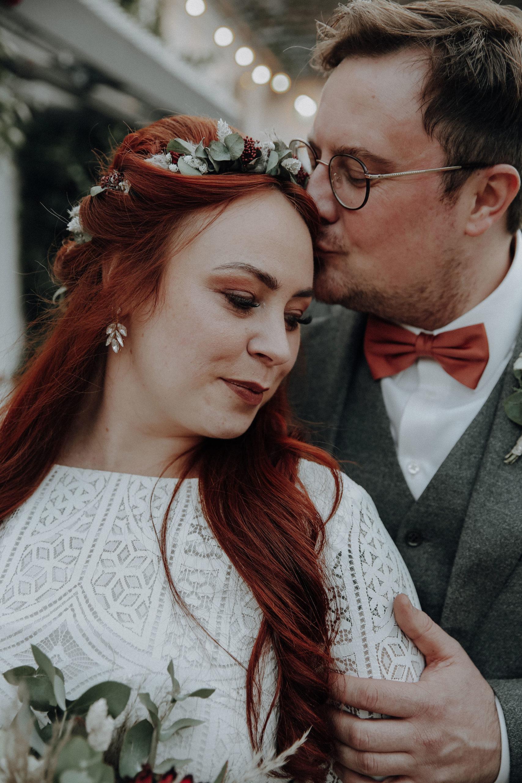 noni Brautmode, Wedding Shoot, Bräutigam küsst Braut auf die Stirn. Nahaufnahme