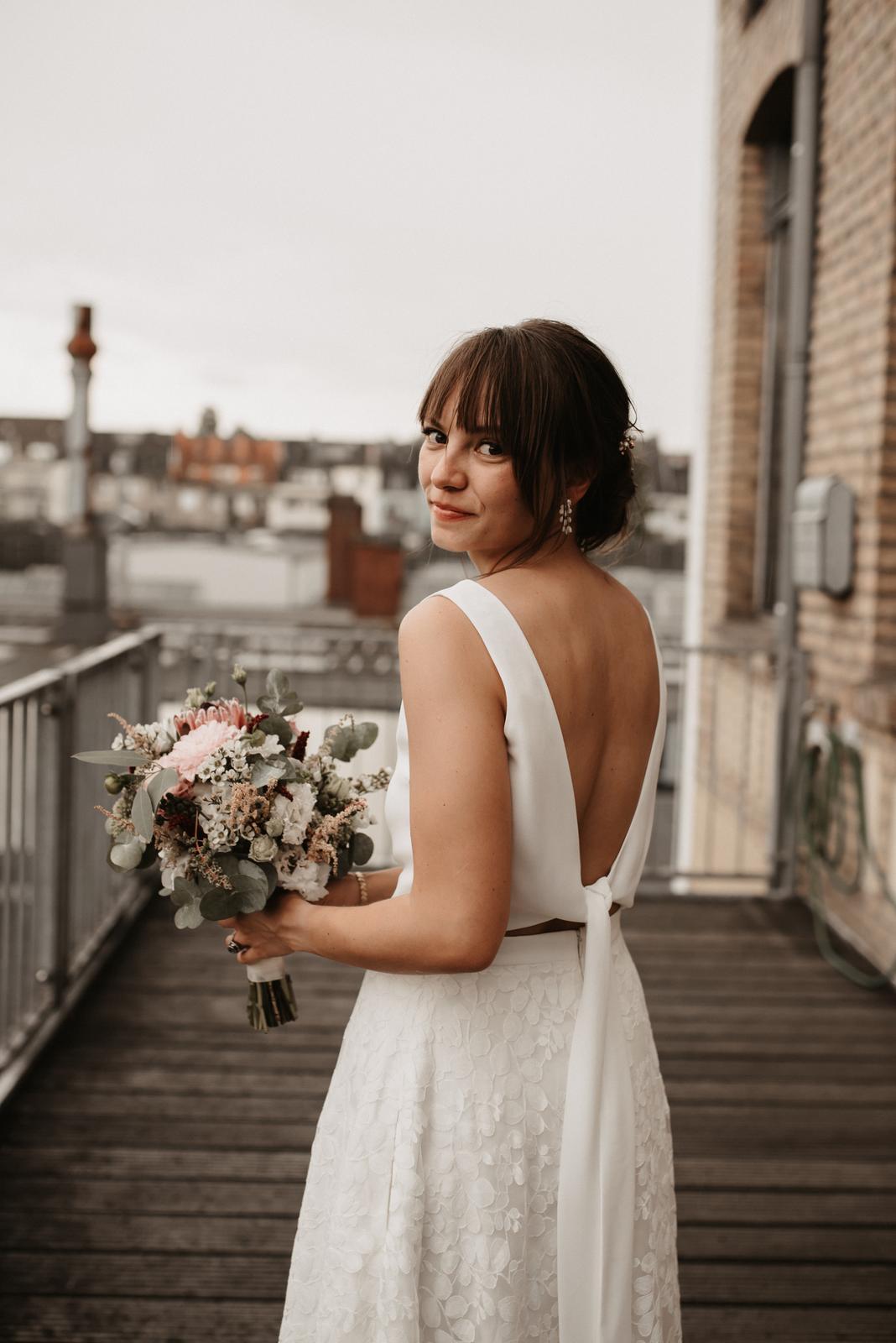 Hochzeitslocation, Braut mit Brautstrauss auf Balkon, Rückenansicht