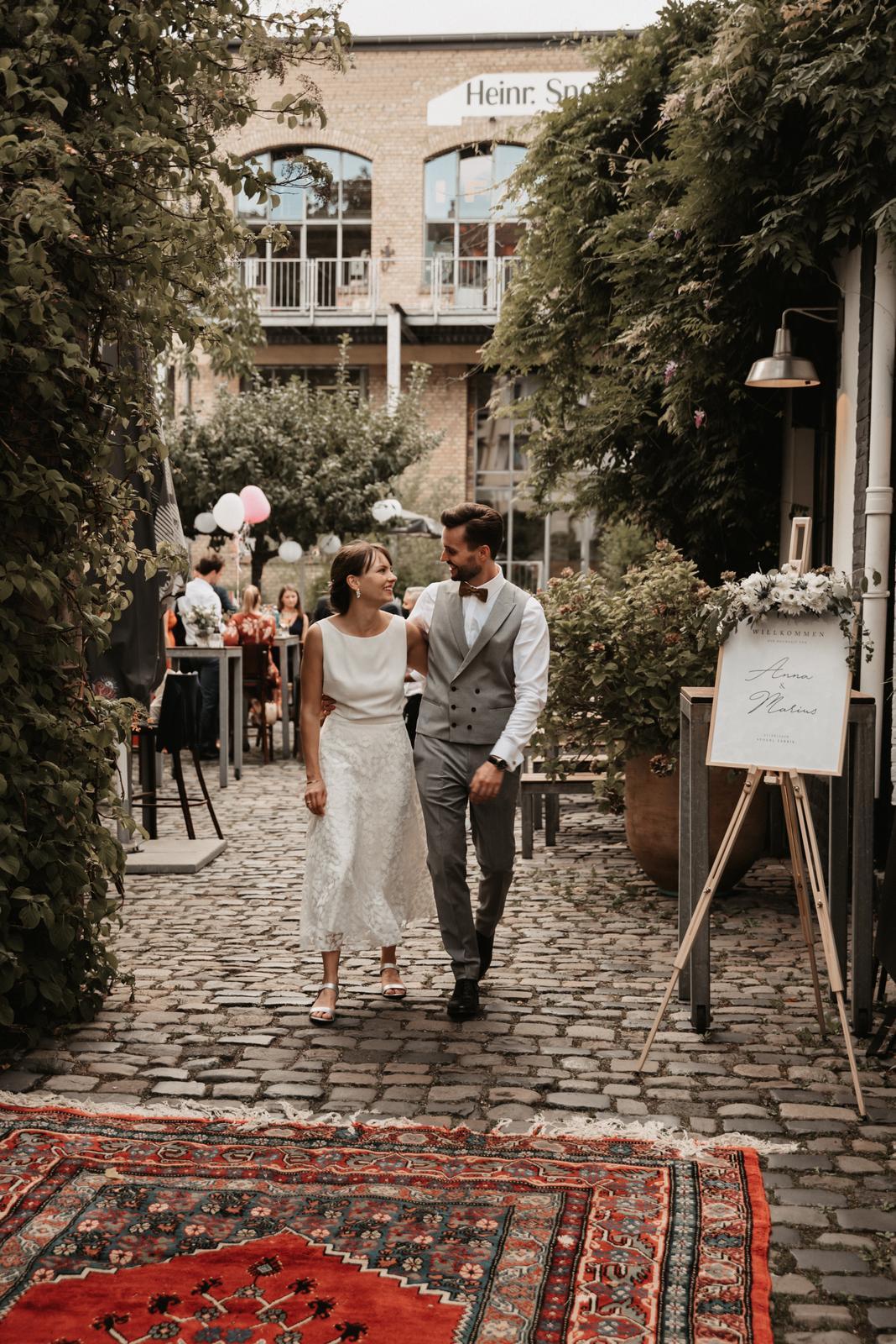 Hochzeitslocation im Innenhof, Brautpaar lachend