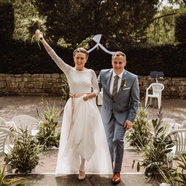 Brautpaar die Treppe hinaufsteigend, Frontalansicht, Braut mit Strauss und langem, weißen Brautkleid mit geometrischem Muster und metallic-roségoldenem Taillengürtel, Bräutigam mit blau-grauem Anzug