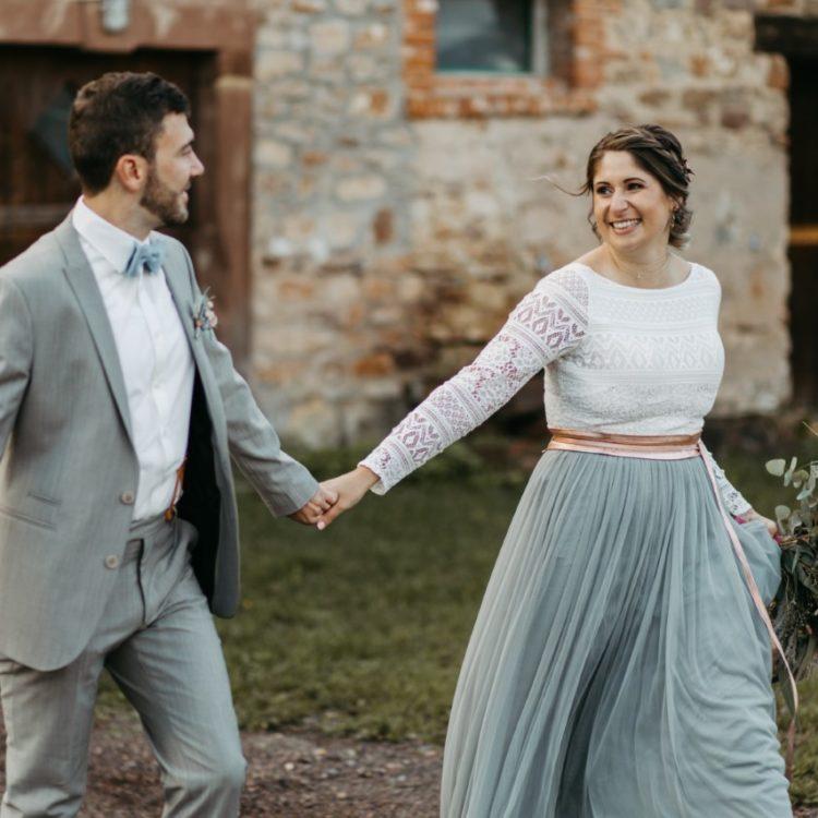 noni Brautmode, Brautpaar im Freien, händchenhaltend und lachend, Braut mit Blumenstrauss