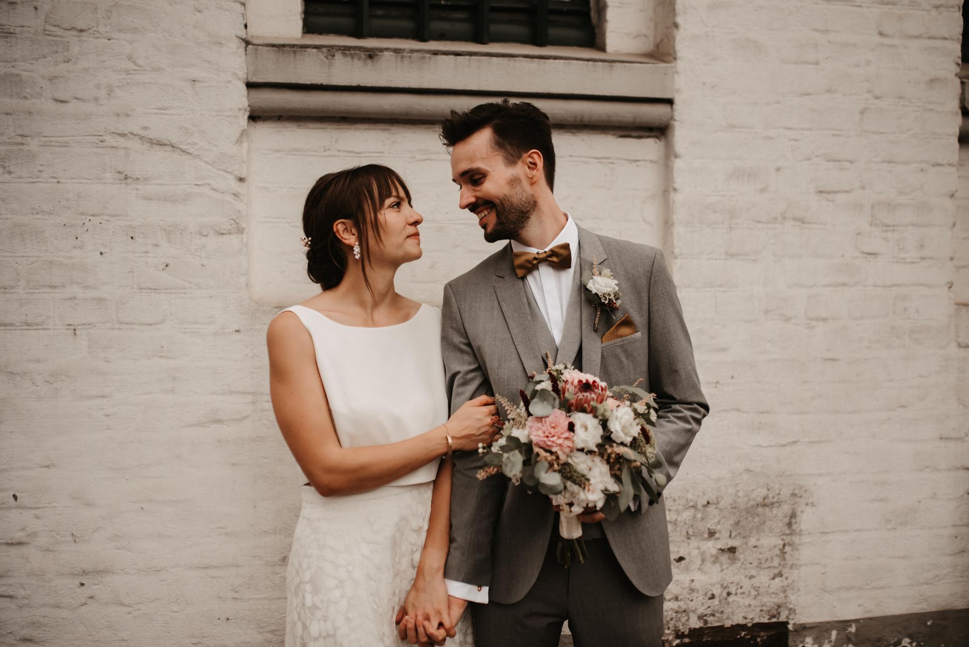 Brautpaar lachend, rückenfreies Brautkleid, Brautstrauss aus Trockenblumen mit Eukalyptus