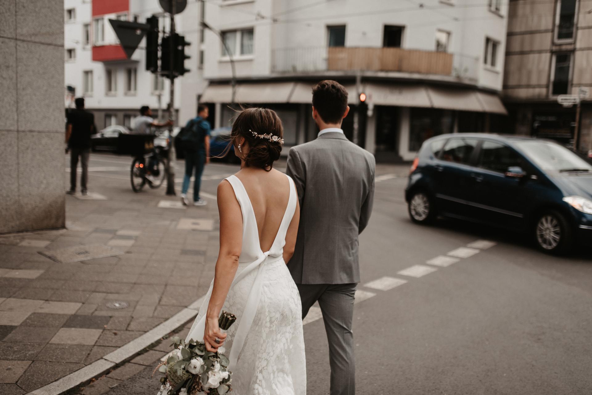 Brautpaar händchenhaltend auf der Strasse, Rückenansicht