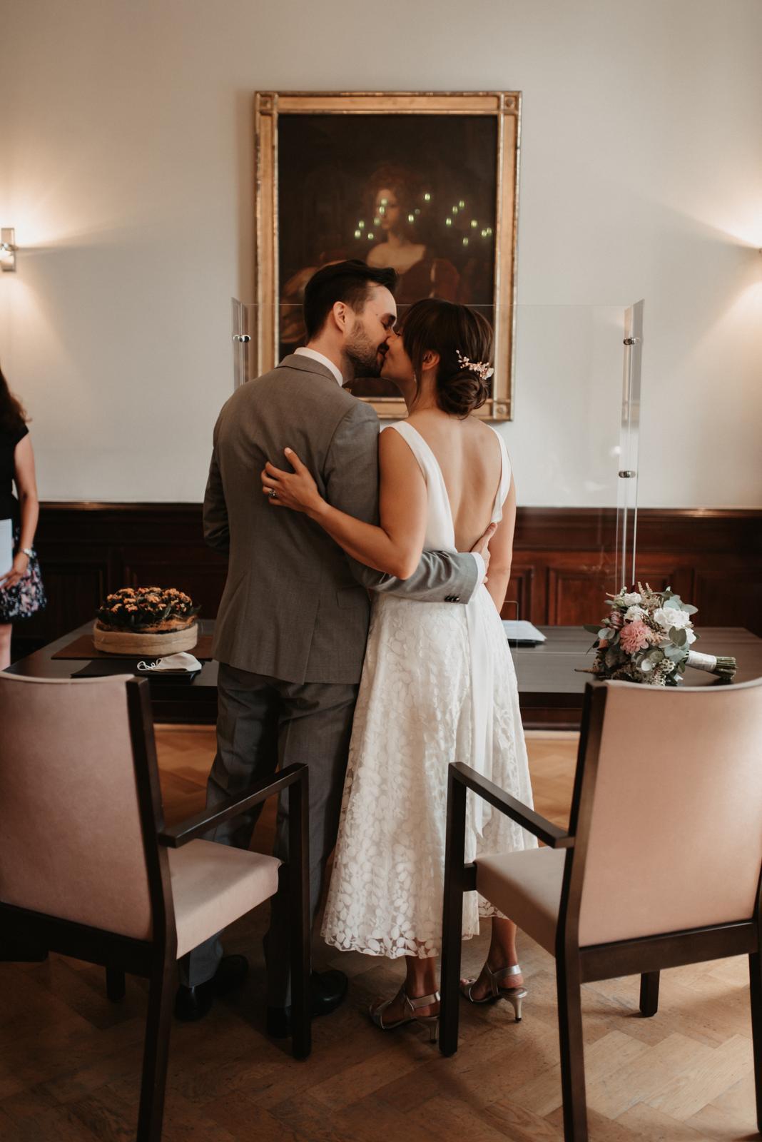 Brautpaar, sich küssend, auf dem Standesamt, Bräutigam mit braunem Anzug, Braut in rückenfreiem, zweiteiligem Brautkleid in Ivory