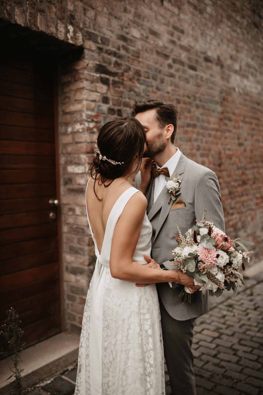 Brautpaar küssend, rückenfreies Brautkleid, Brautstrauss aus Trockenblumen mit Eukalyptus