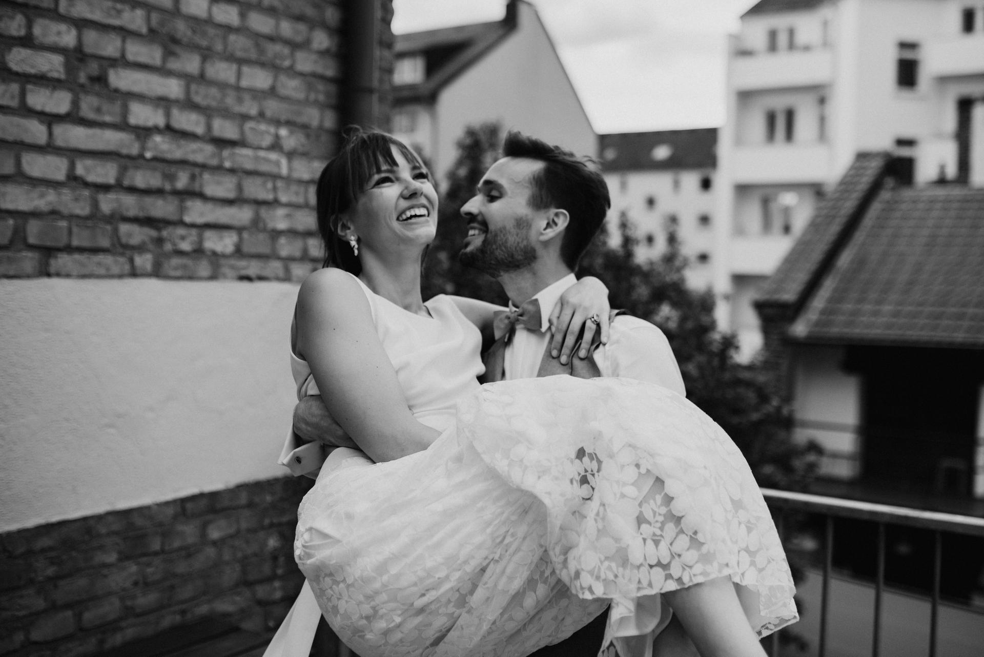 Brautpaar auf Balkon, Bräutigam  Braut tragend, lachend, schwarz weiss