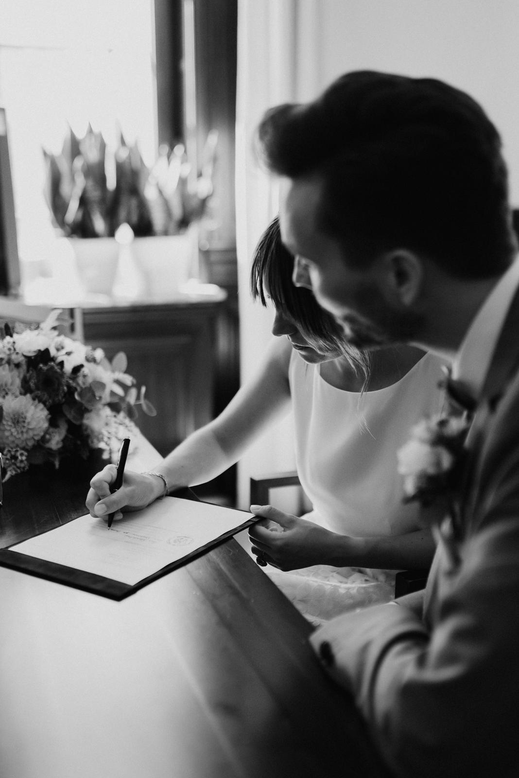 Brautpaar am Standesamt, Unterschrift der heiratsurkunde, schwarz-weiss
