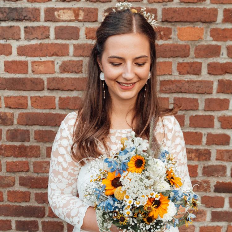 noni Brautmode, Braut mit buntem Blumenstrauss, Blumenhaarschmuck im Boho Stil und halb-transparentem Spitzentop