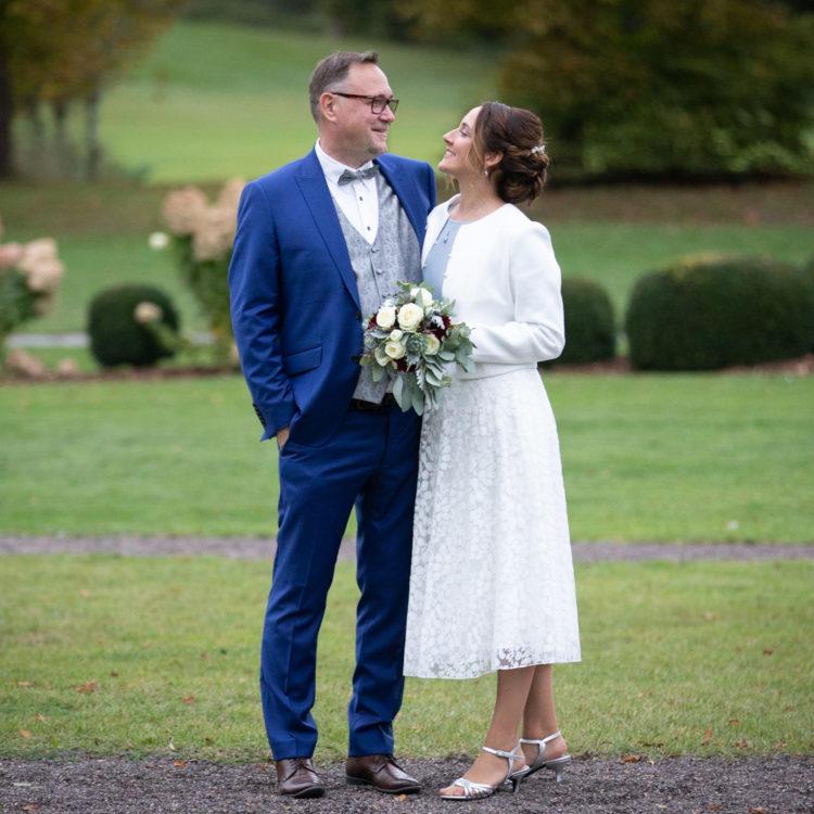 Brautpaar sich anlächelnd vor grüner Wiese