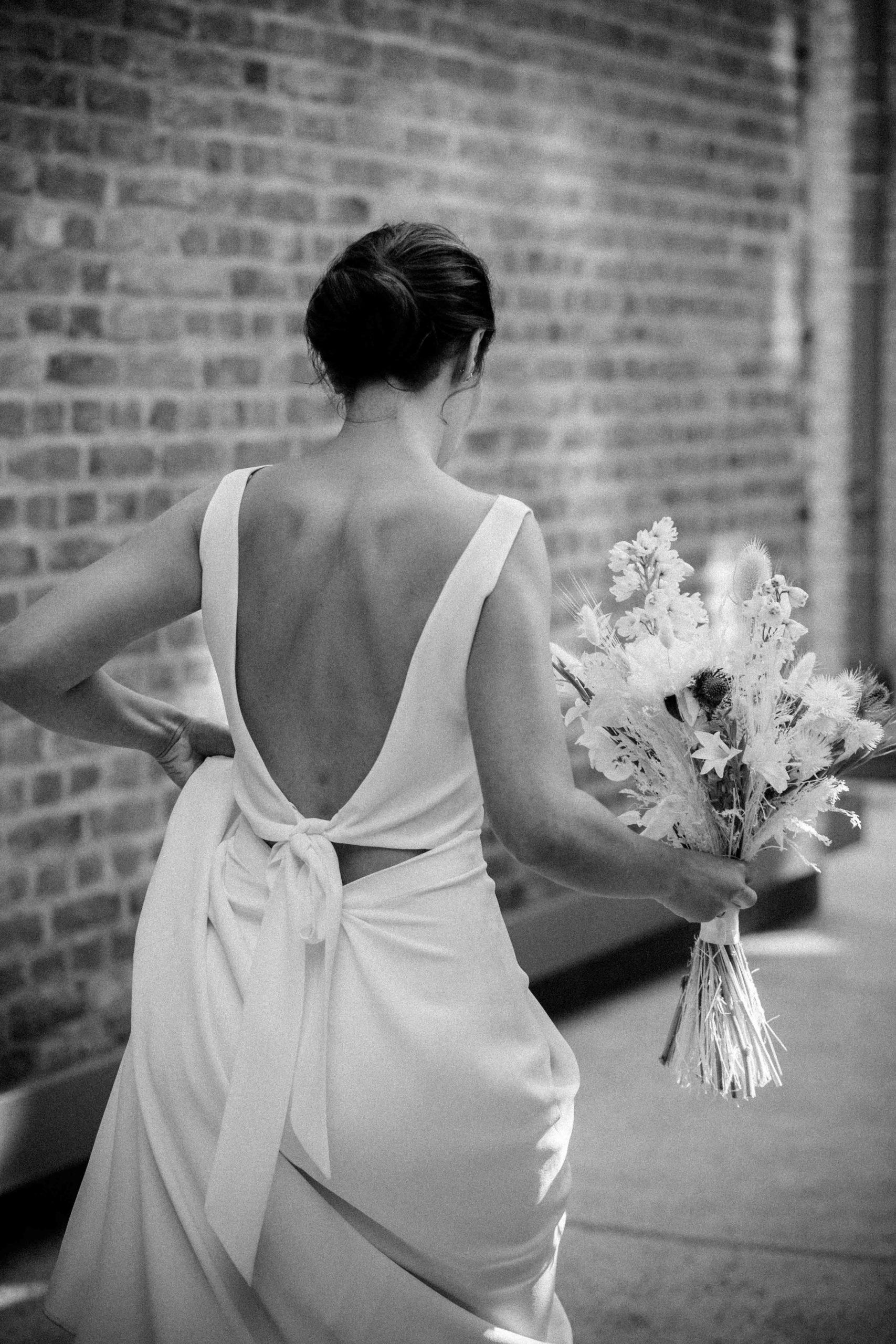 Schwarz-weiss Fotografie, Model mit rückenfreiem Brautkleid mit V-Ausschnitt, Rückenansicht, Hochformat