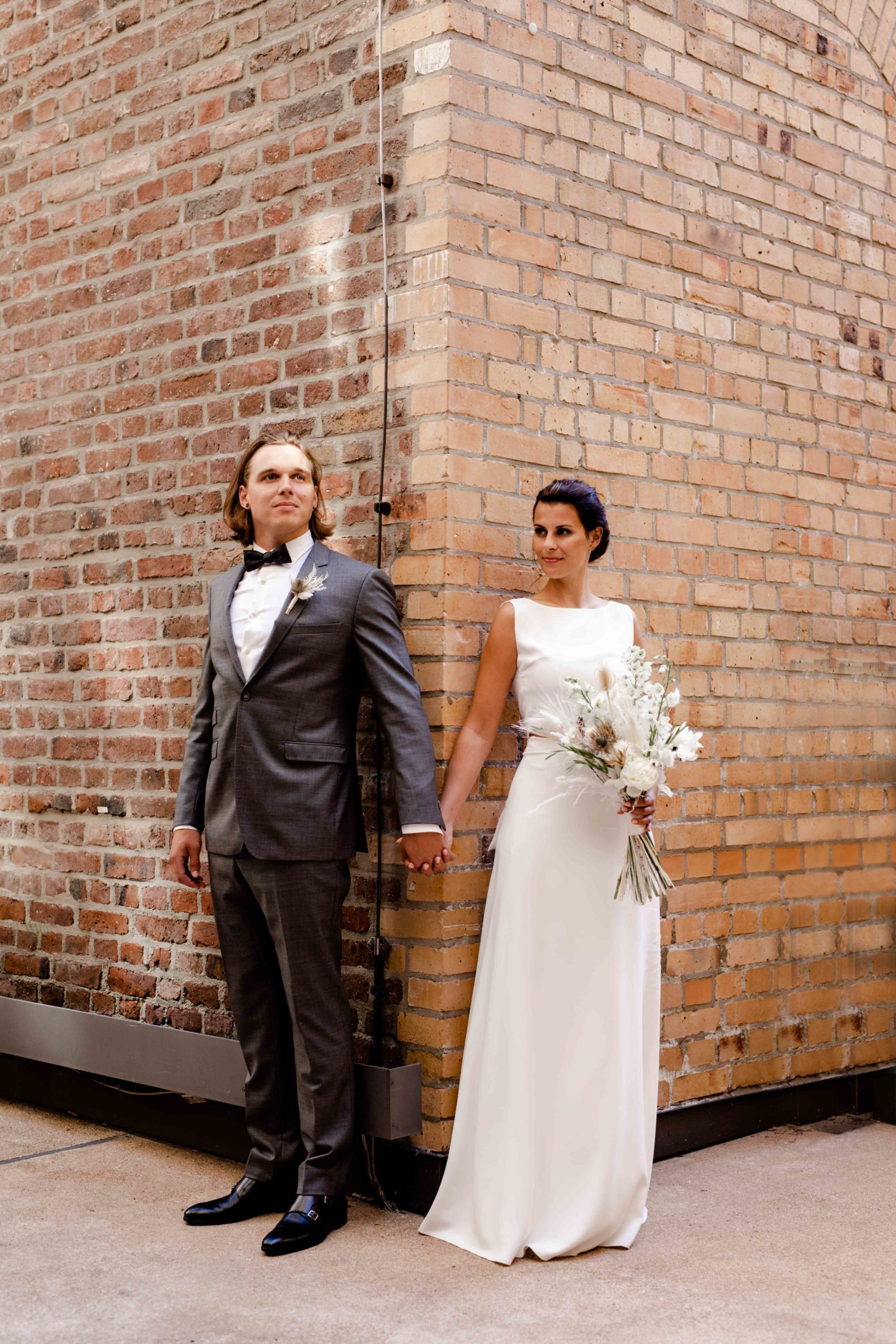 Styled Shoot Brautmode, Model-Brautpaar händchenhaltend in Hochzeitsgarderobe mit Brautstrauss vor Backsteinmauer