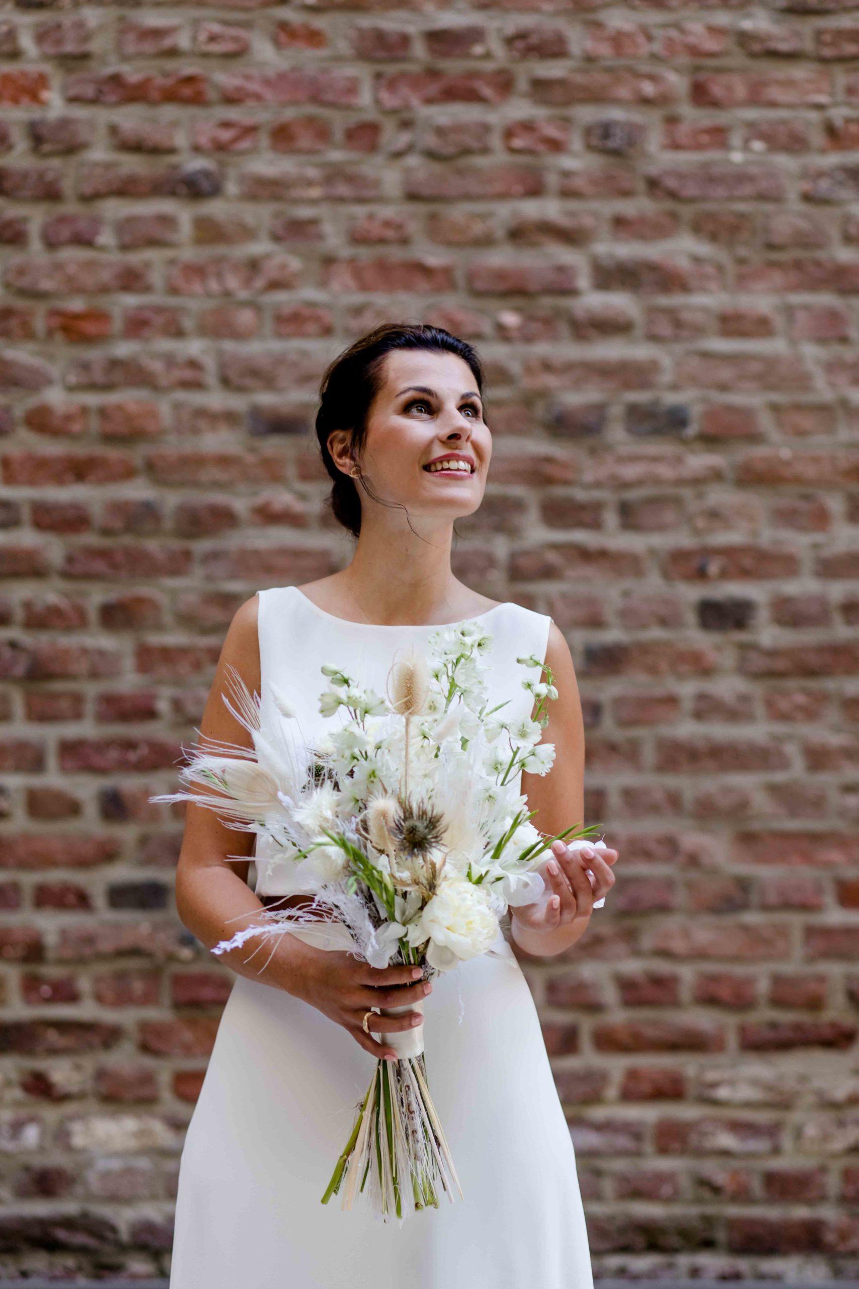 Styled Shoot Brautmode, Model mit weißem, ärmellosen Brautkleid mit Brautstrauss vor Backsteinmauer