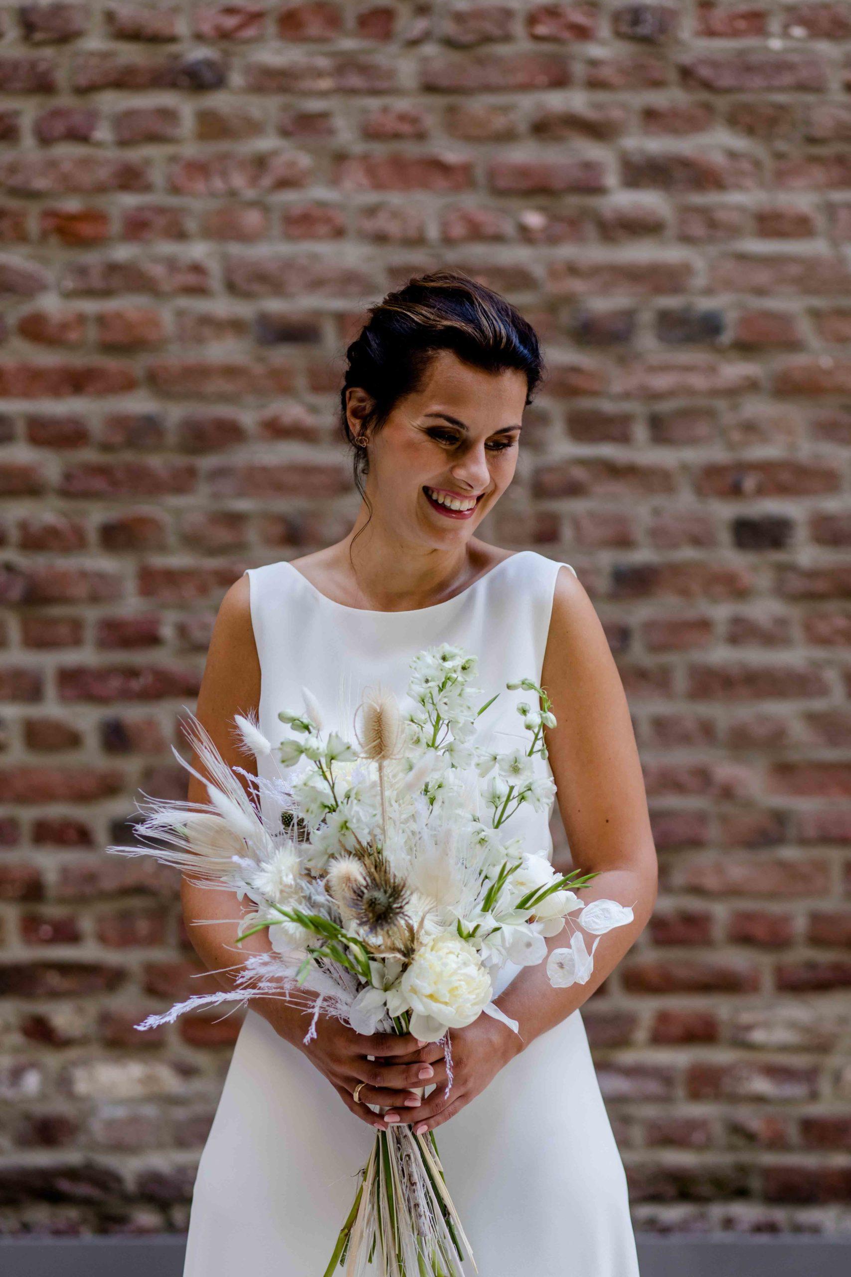 Styled Shoot Brautmode, Model mit weißem, ärmellosen Brautkleid mit Brautstrauss vor Backsteinmauer, lachend