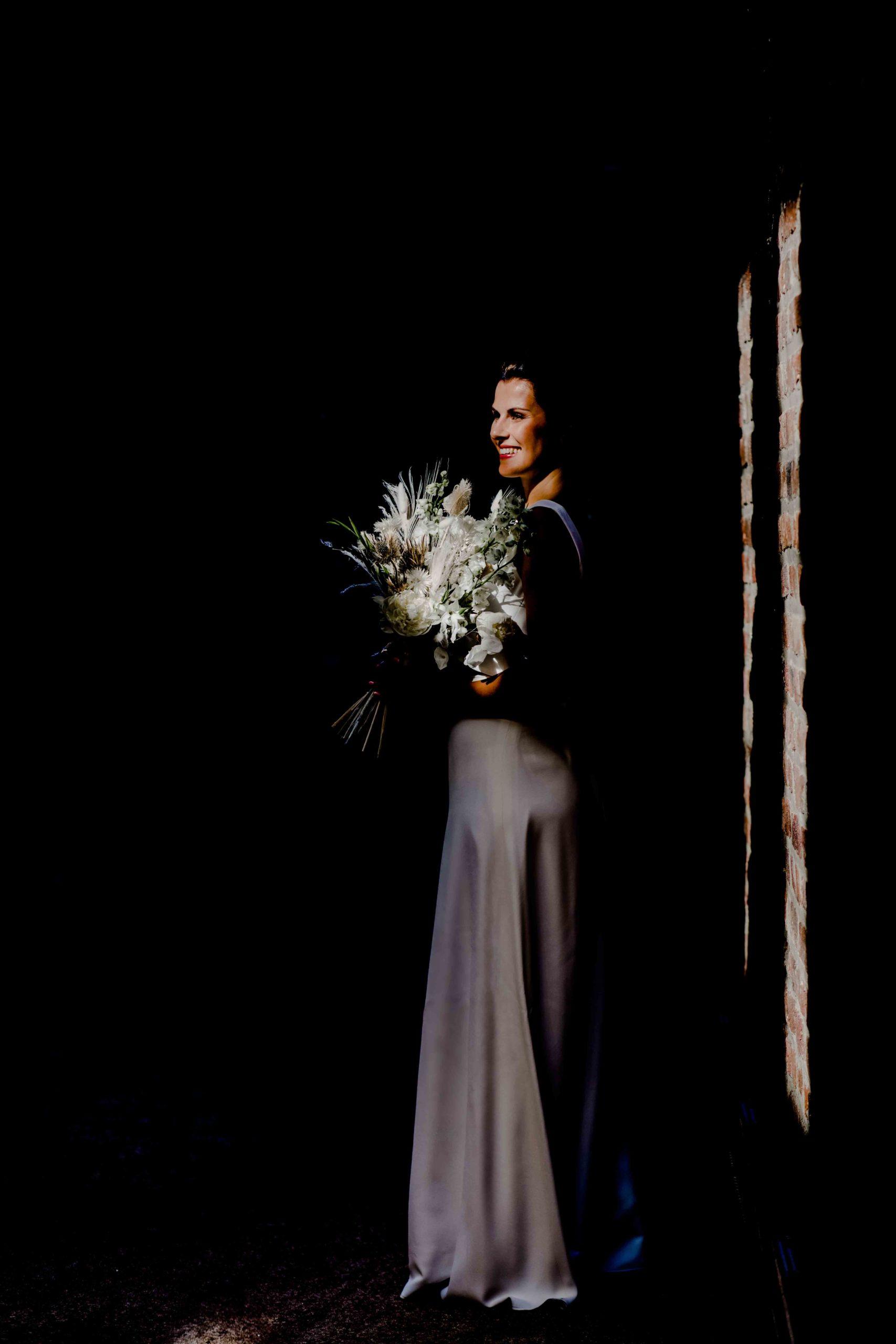 Styled Shoot Brautmode, Model mit weißem, ärmellosen Brautkleid mit Brautstrauss