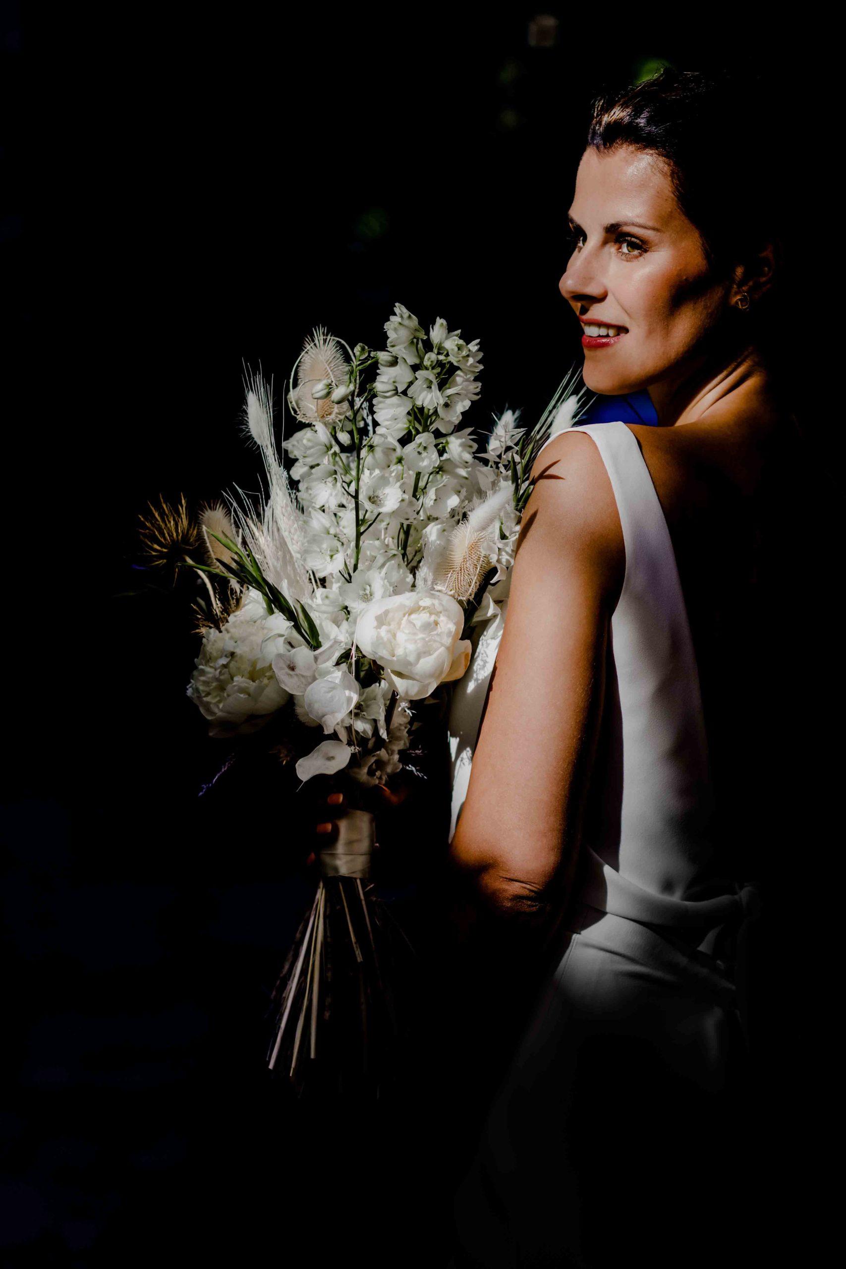 Styled Shoot Brautmode, Model mit weißem, ärmellosen Brautkleid mit Brautstrauss, Nahaufnahme mit halber Rückenansicht