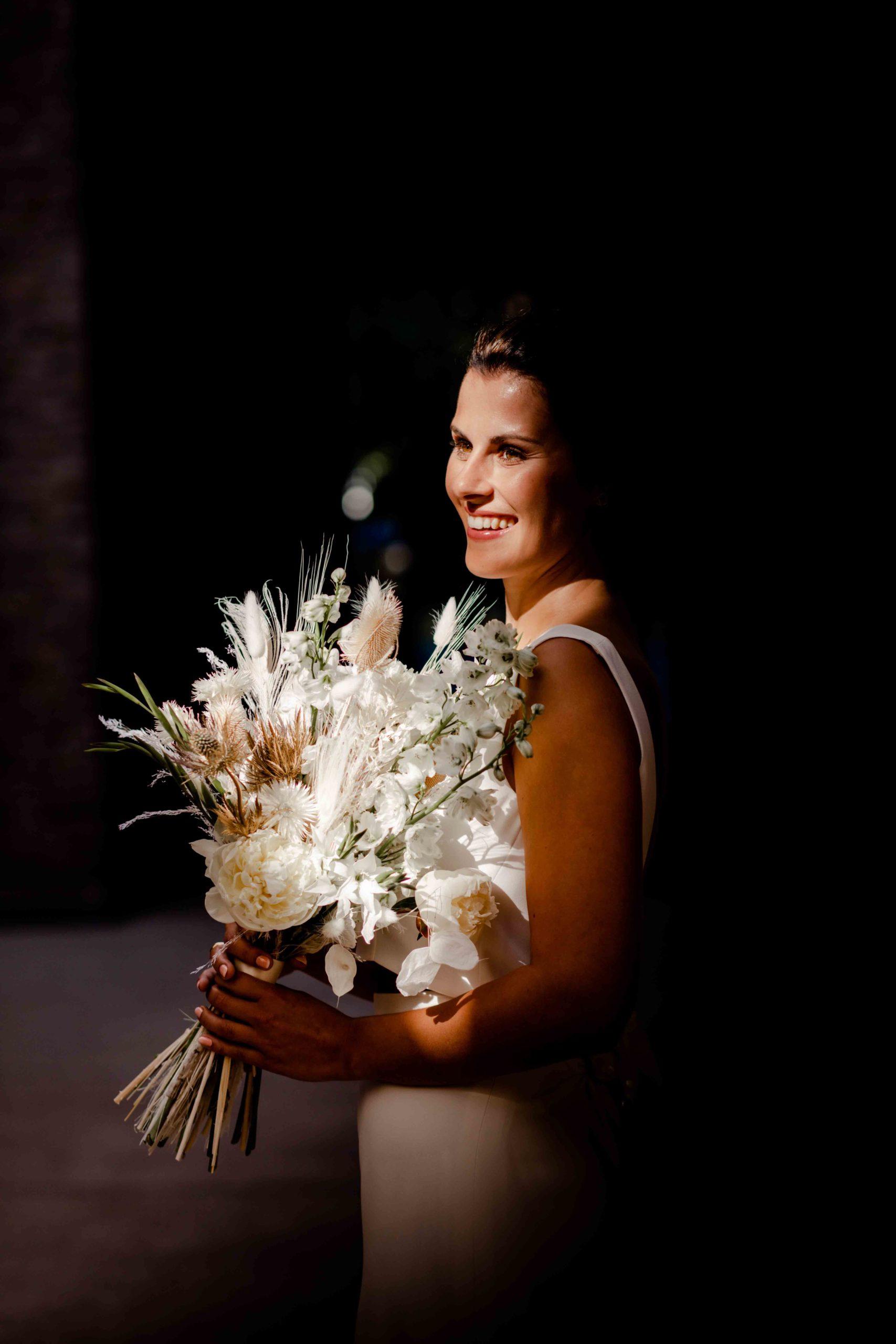 Styled Shoot Brautmode, Model mit weißem, ärmellosen Brautkleid mit Brautstrauss, Seitenansicht
