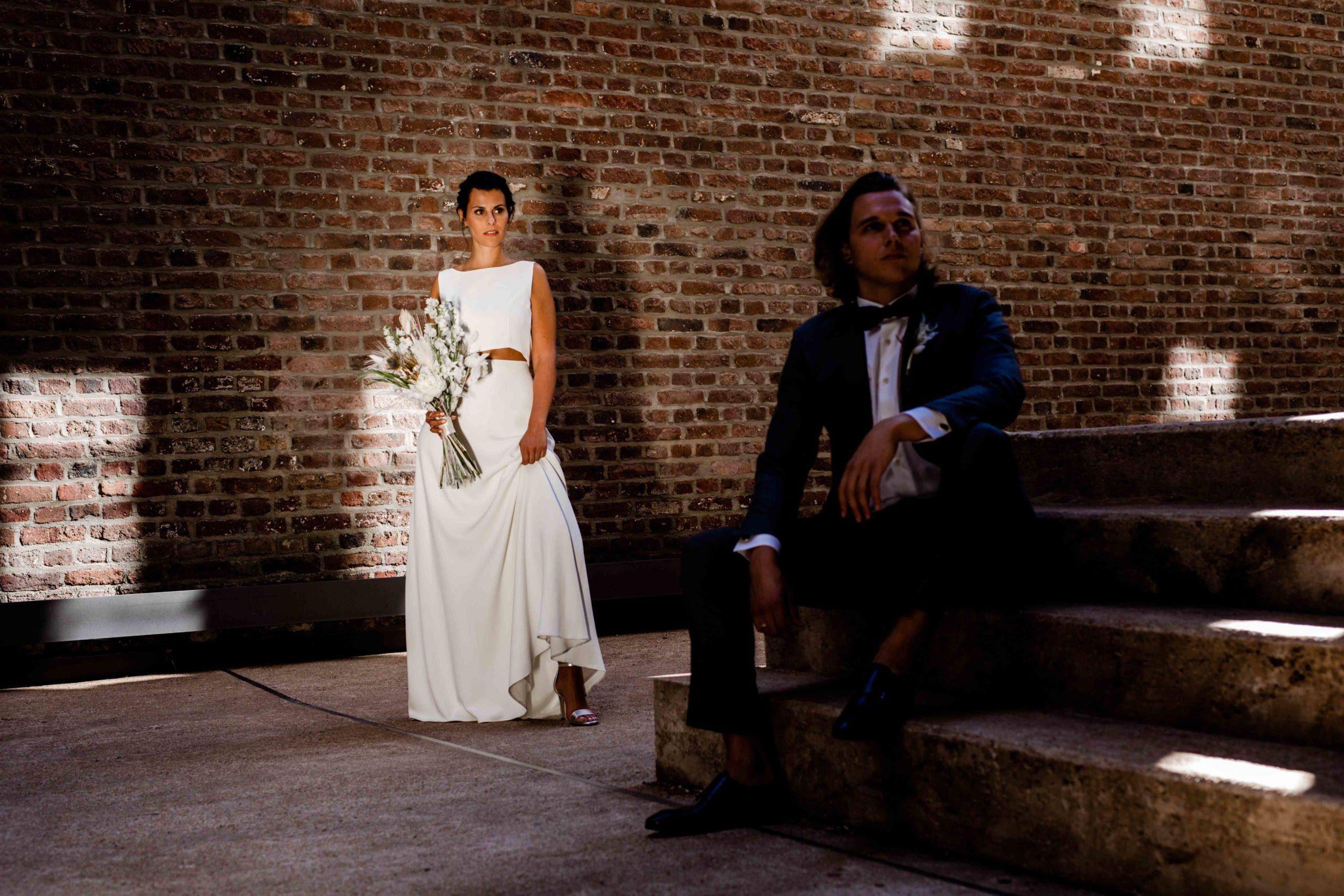 Styled Shoot Brautmode, Model-Brautpaar in Hochzeitsgarderobe mit Brautstrauss vor Backsteinmauer, Bräutigam auf Treppen sitzend