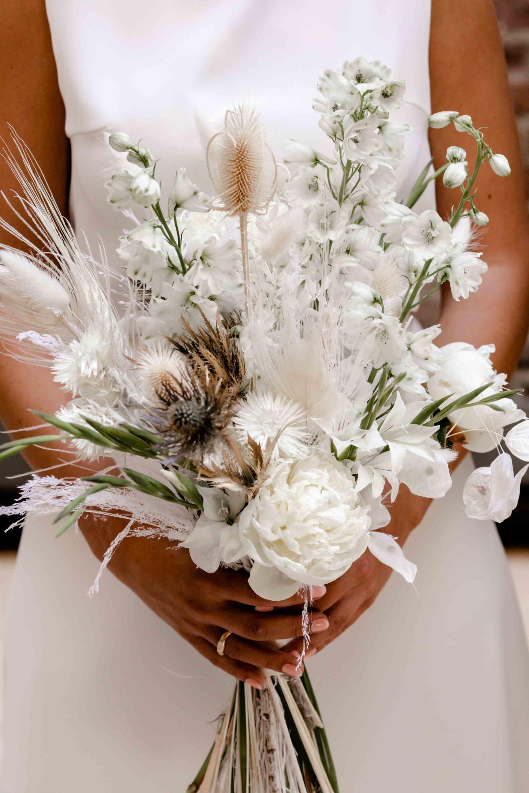 Styled Shoot Brautmode, Model mit Brautkleid, Brautstrauss in Kamera haltend, Nahaufnahme