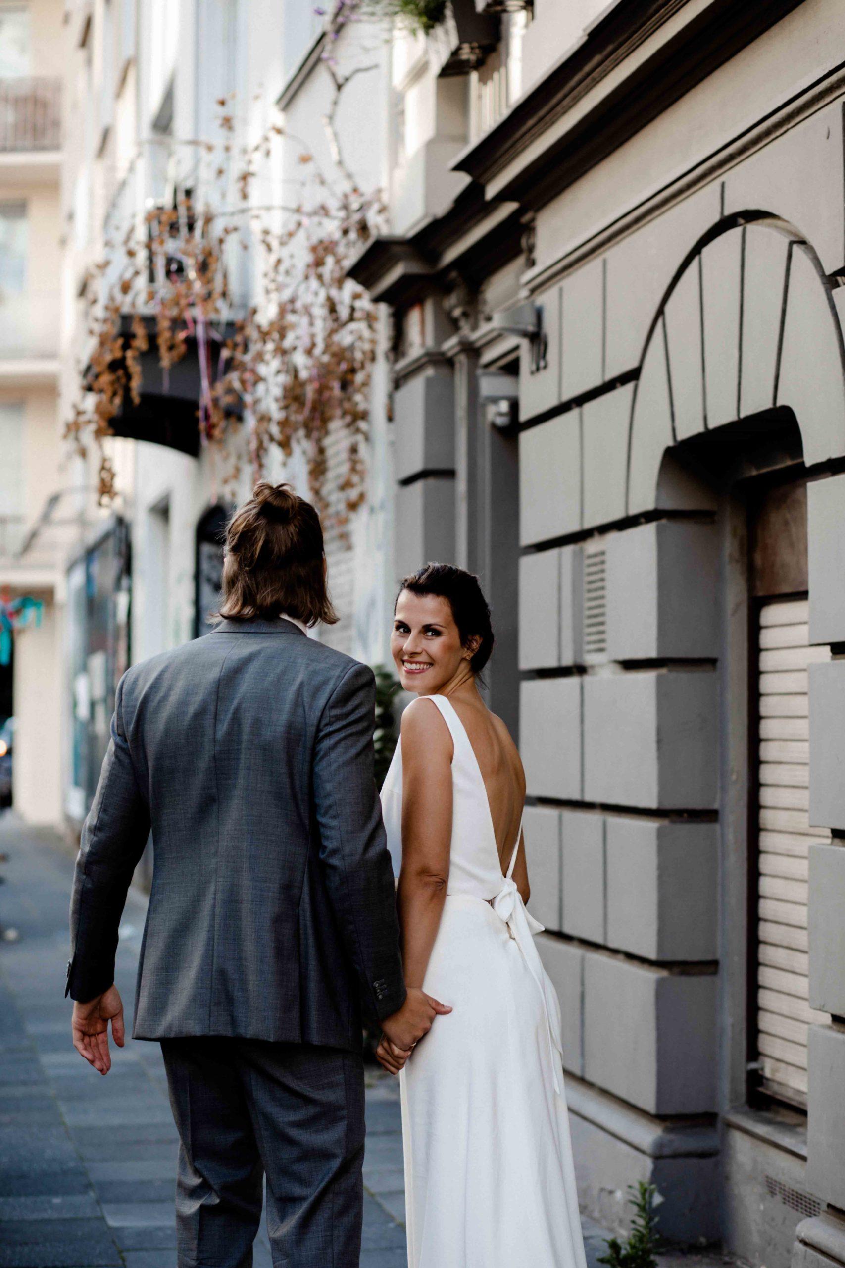 Styled Shoot Brautmode, Model-Brautpaar Händchenhaltend auf Strasse