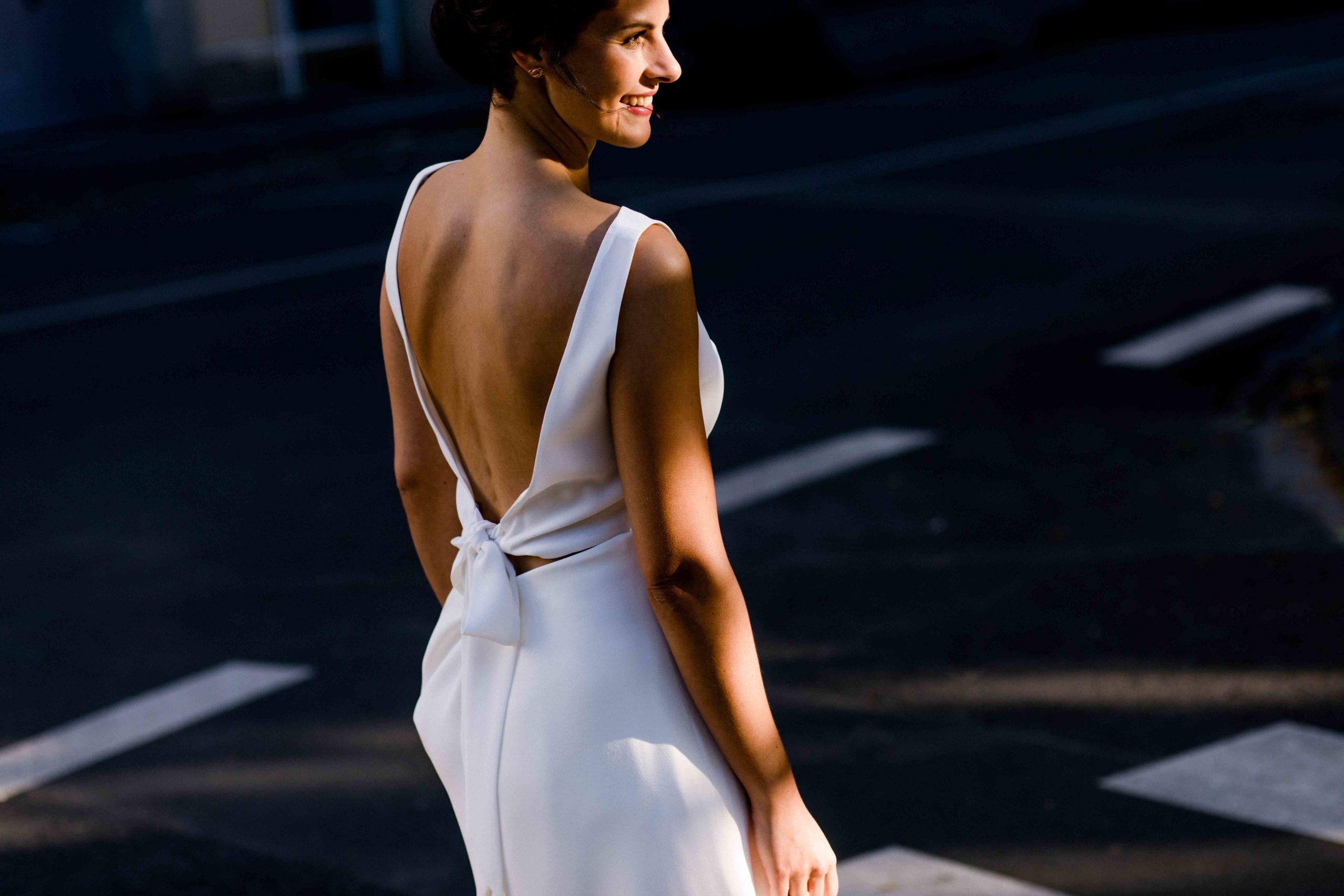 Styled Shoot Brautmode, Model mit rückenfreiem und ärmellosem Brautkleid auf Strasse