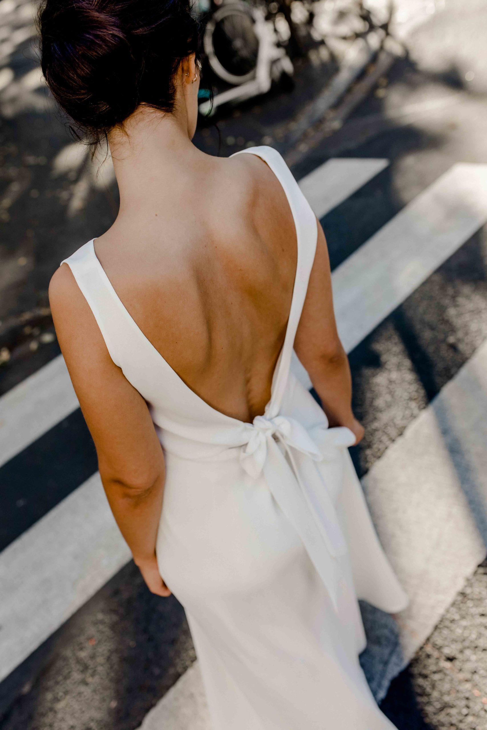 Styled Shoot Brautmode, Model mit rückenfreiem und ärmellosem Brautkleid auf Zebrastreifen