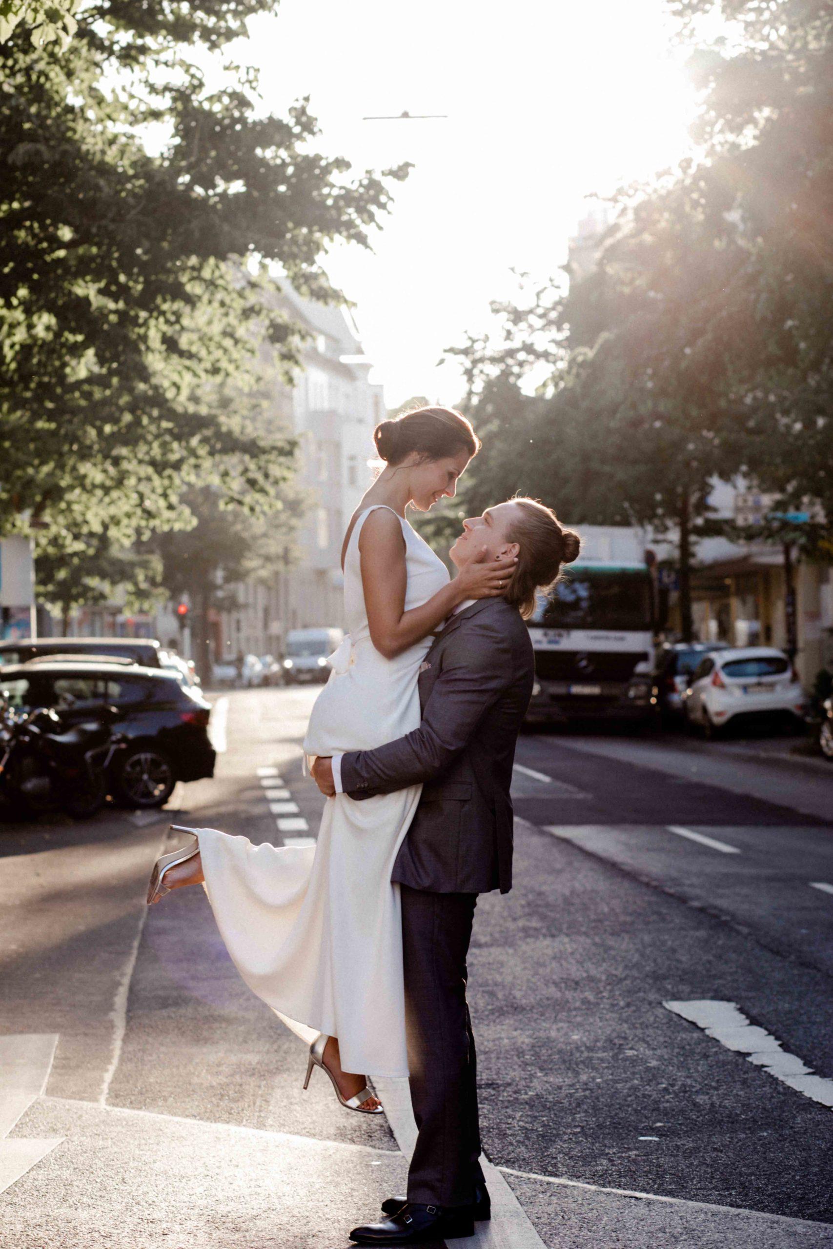 Styled Shoot Brautmode, Bräutigam hievt Braut in die Luft auf Strasse, lachend