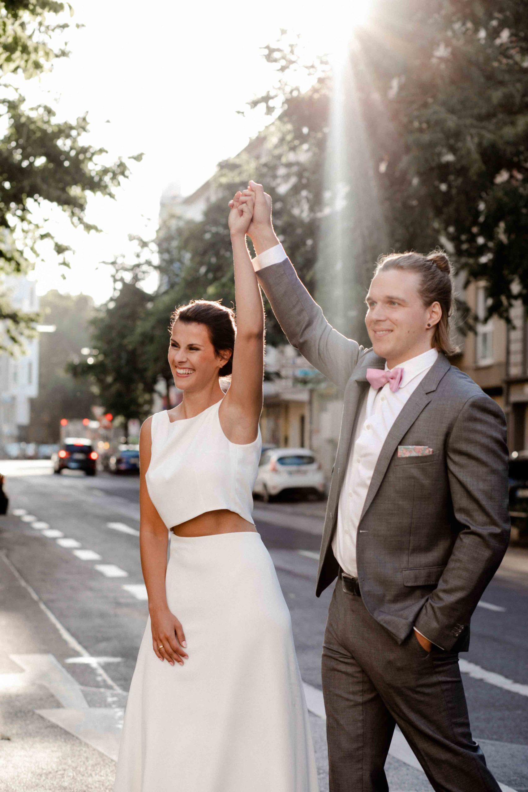 noni Brautmode Styled Shoot, Brautpaar Händchenhaltend, Arme in die Luft gestreckt, auf Strasse