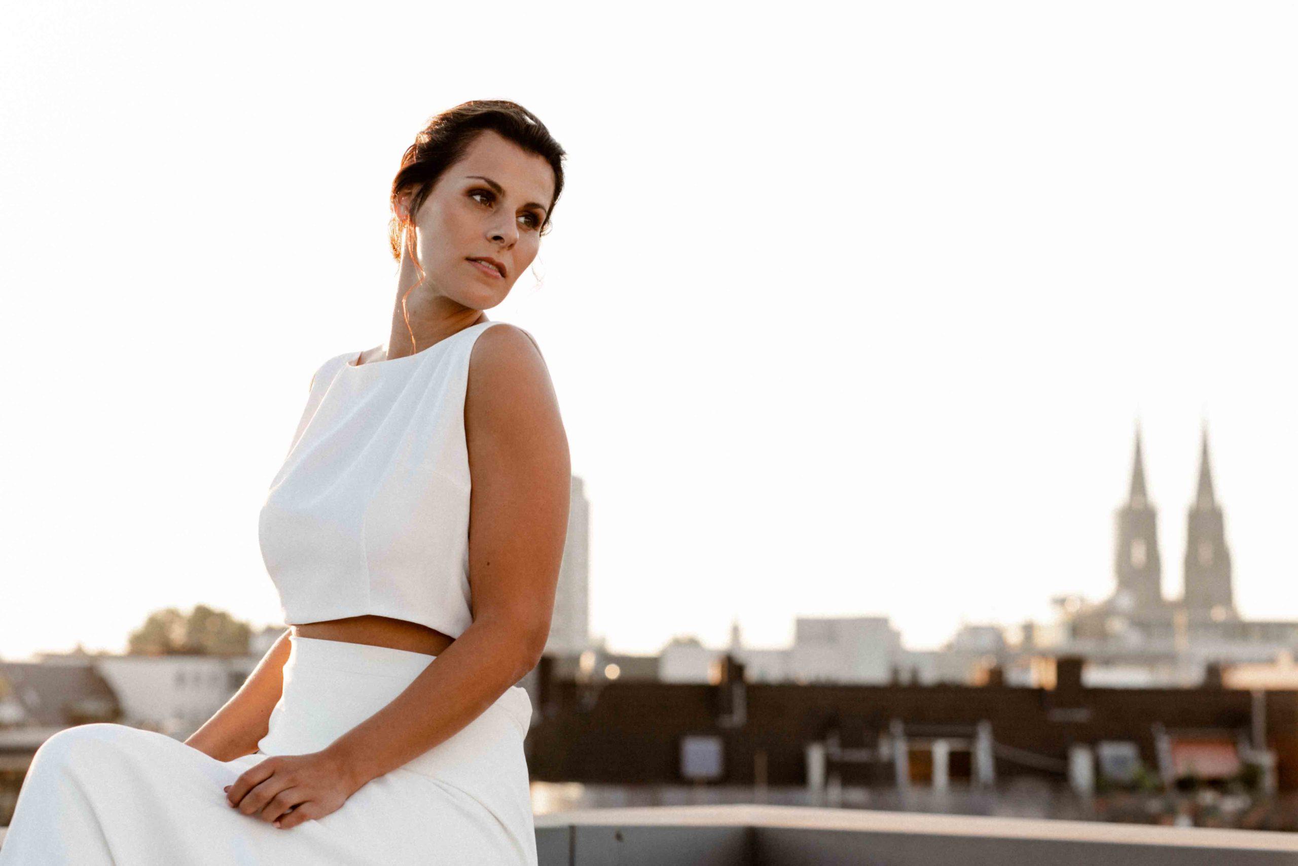 Styled Shoot Brautmode, Model in weißem Hochzeitskleid auf Hochhausterrasse