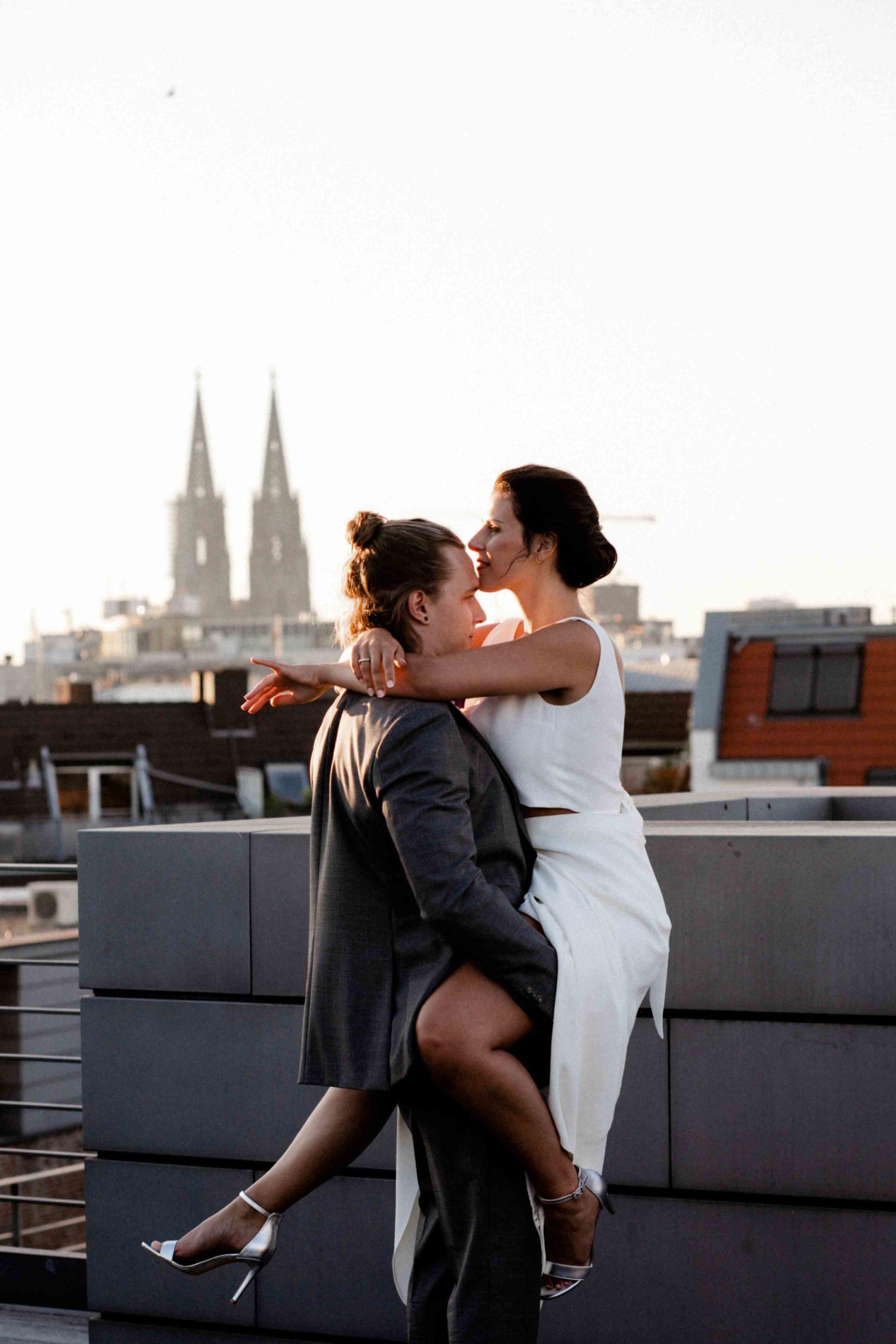 Styled Shoot Brautpaar sich umarmend auf Hochhausterrasse, mit Großstadtdächern und Kölner Domspitzen im Hintergrund