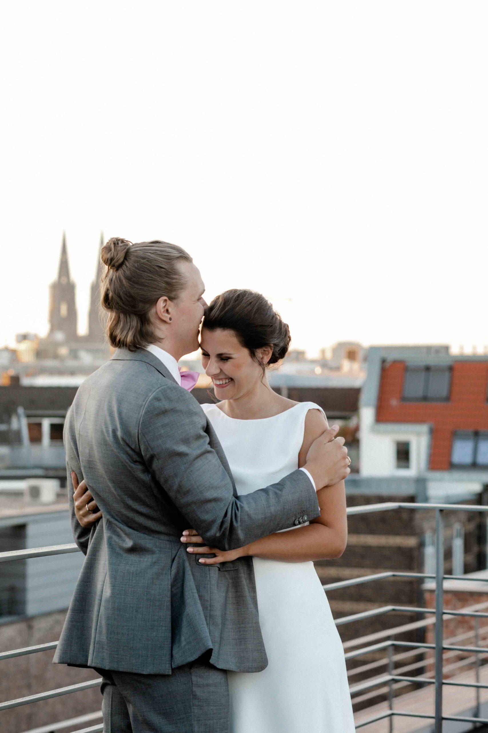 Styled Shoot Brautpaar sich umarmend auf Hochhausterrasse mit Kölner Dom und Großstadtdächern im Hintergrund