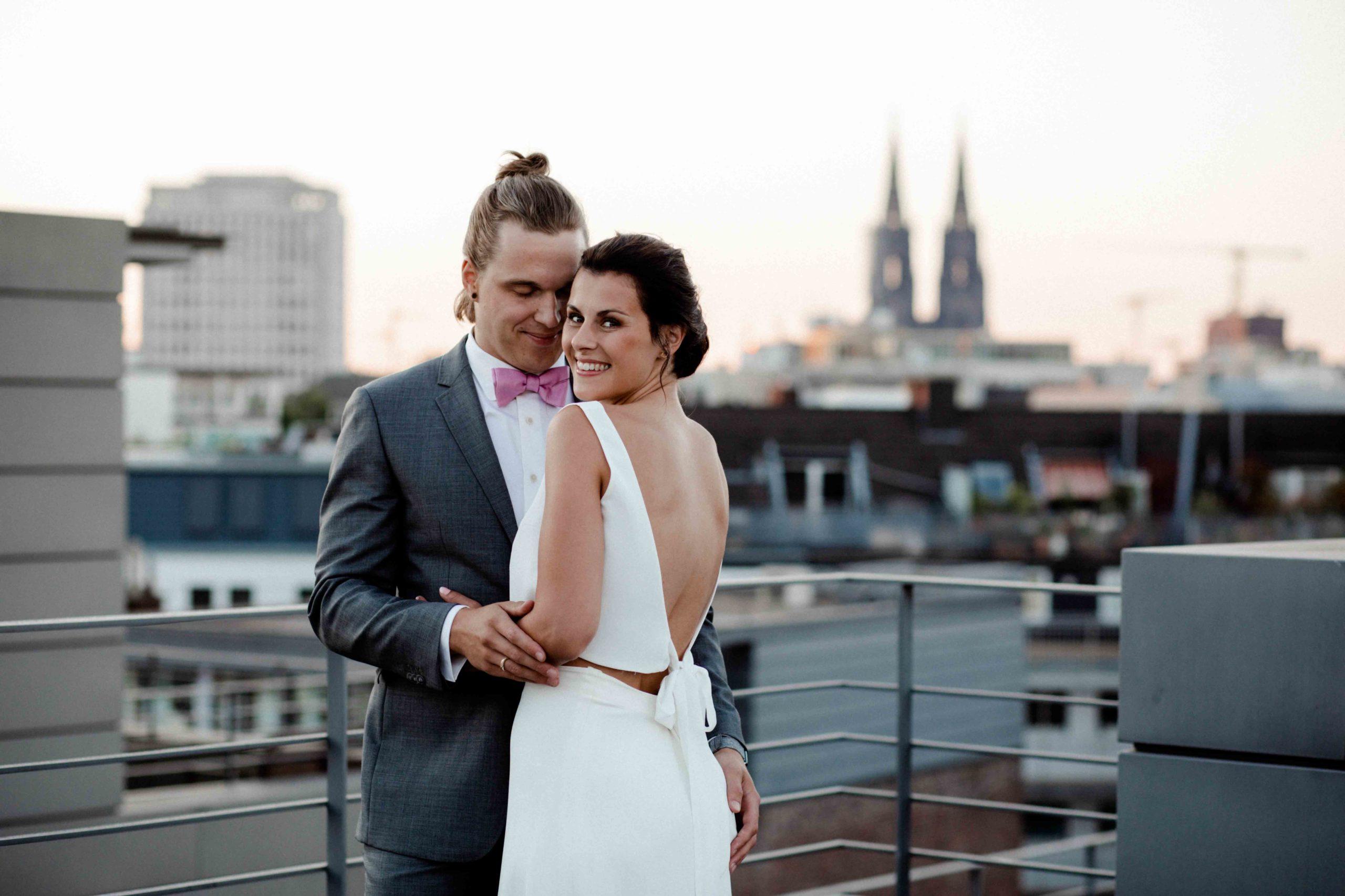 Styled Shoot Brautmode, Hochzeitspaar umarmend und lachend, Braut zur Kamera gewandt mit rückenfreiem Brautkleid in Weiß, Hochhäuser und Kölner Dom im Hintergrund