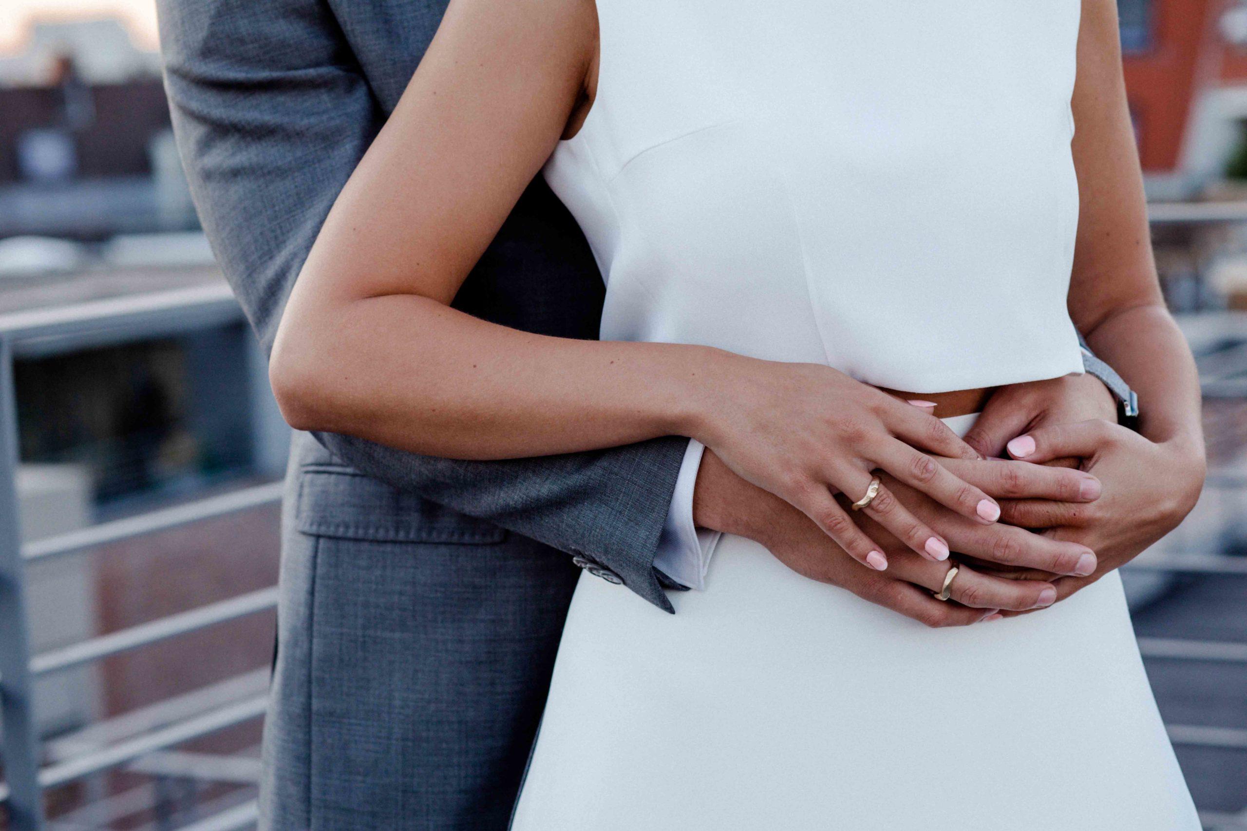 Styled Shoot Brautmode, Bräutigam Braut von hinten umarmend, Detailaufnahme Eheringe an Händen