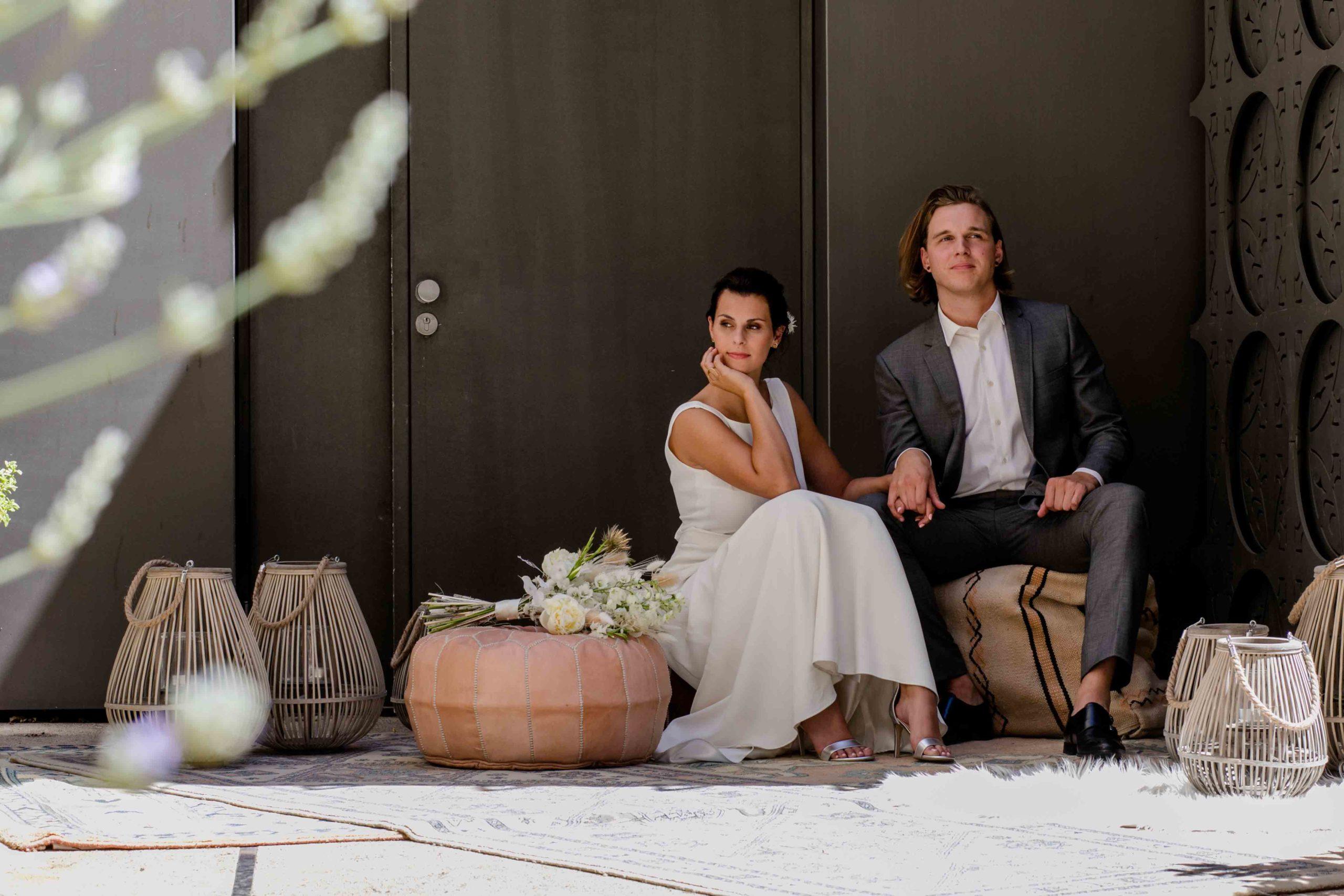 Styled Shoot Brautmode, Model-Brautpaar sitzend inmitten von urbaner Deko