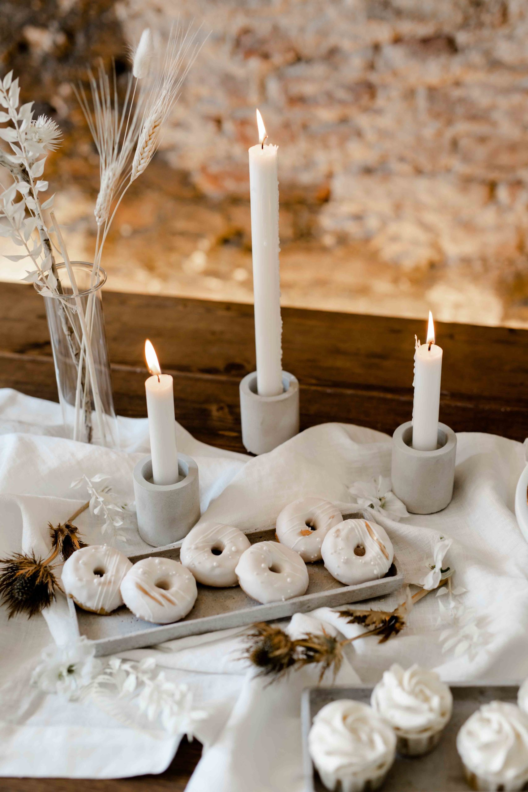 noni Brautmode, Styled Shoot, Tischdekoration für Hochzeit in Weiß mit Kerzenhaltern, weiß-glasierten Mini-Donuts und Trockenblumen