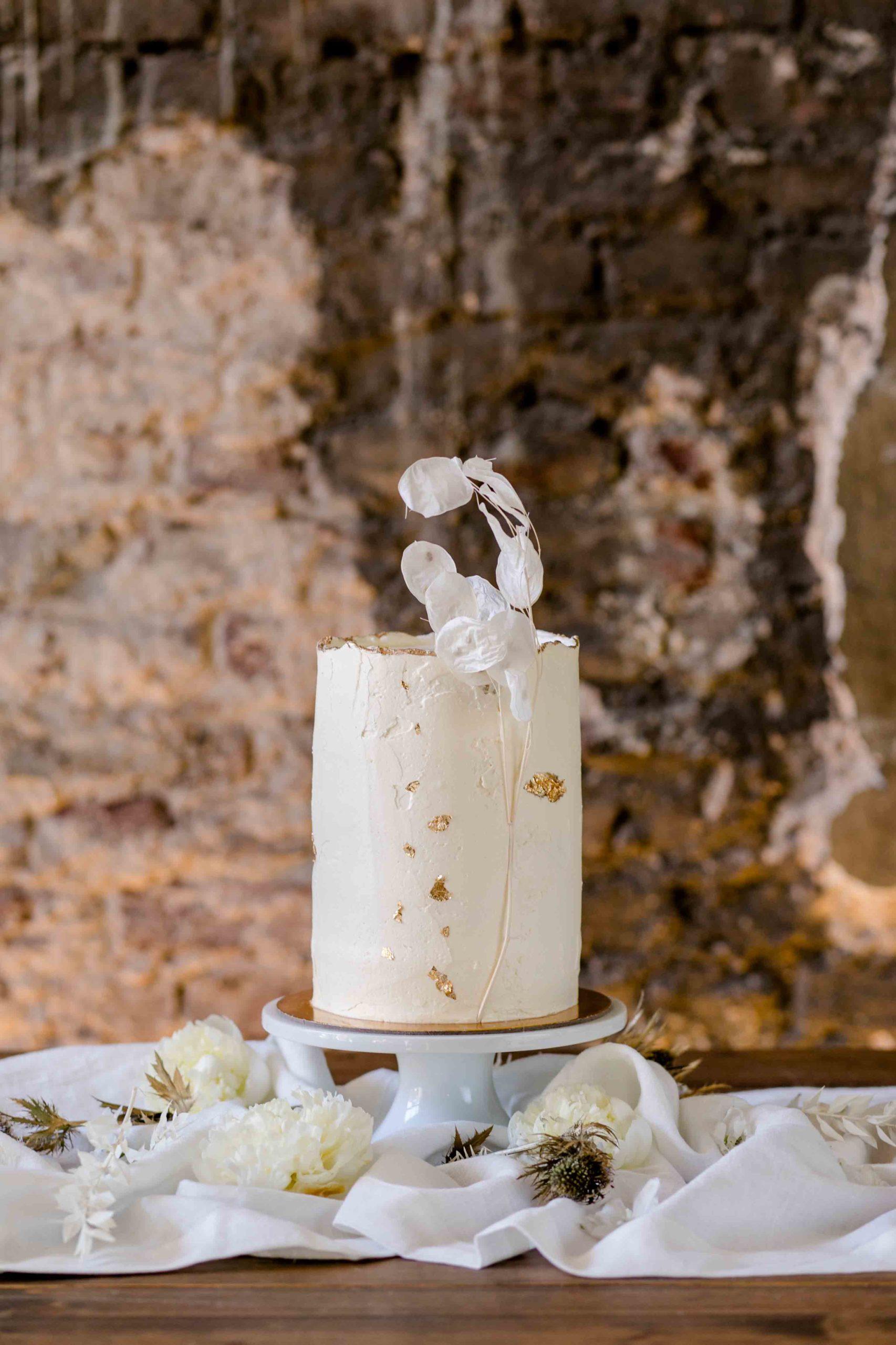 Detailaufnahme Hochzeitstorte im Naked Cake-Stil in Zylinderform vor Wand im Shabby Chic