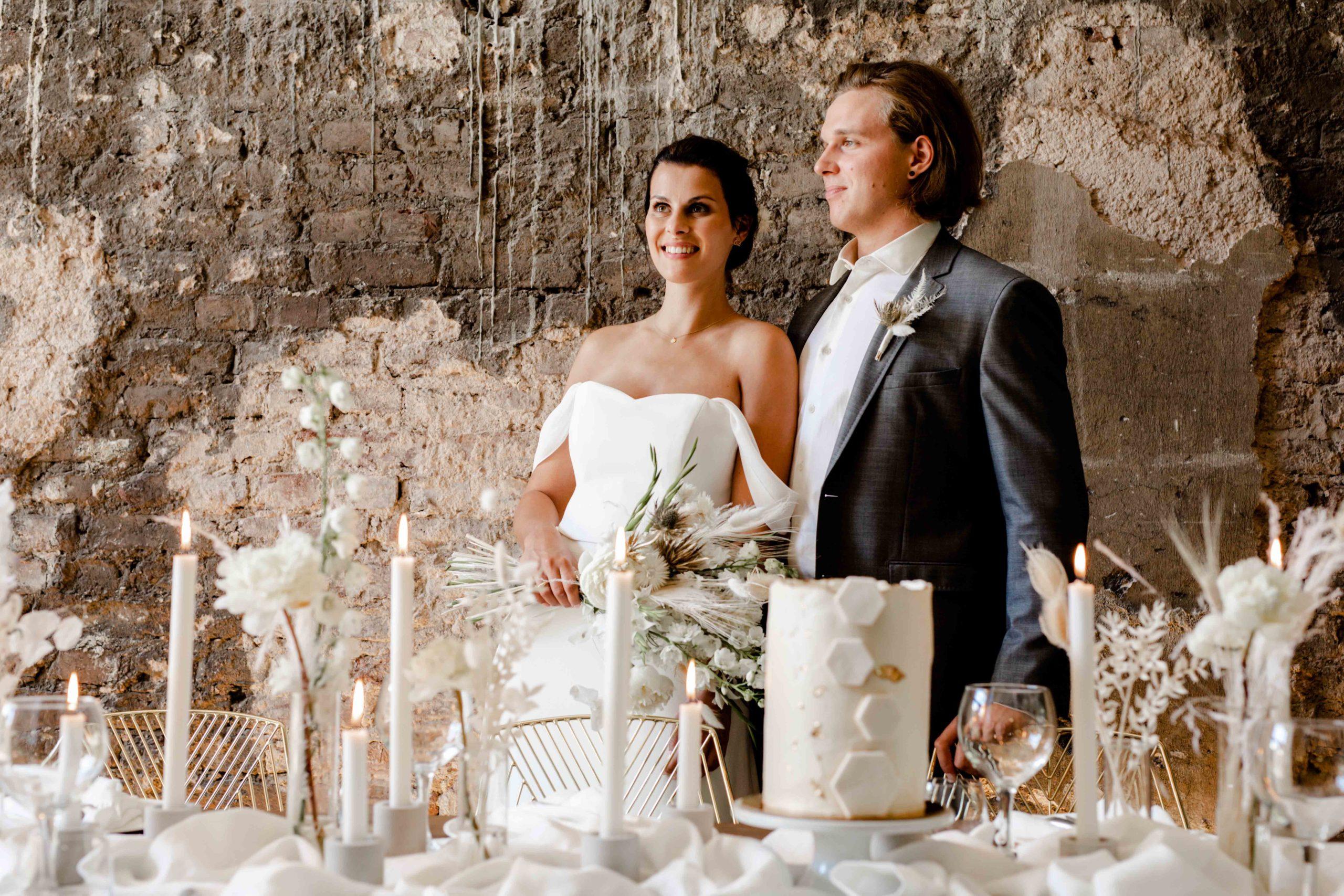 Styled Shoot für Hochzeitsinspiration, Model-Brautpaar an Hochzeitstafel mit weißer Tischdekoration, Naked Cake, Kerzenleuchtern und Trockenblumen