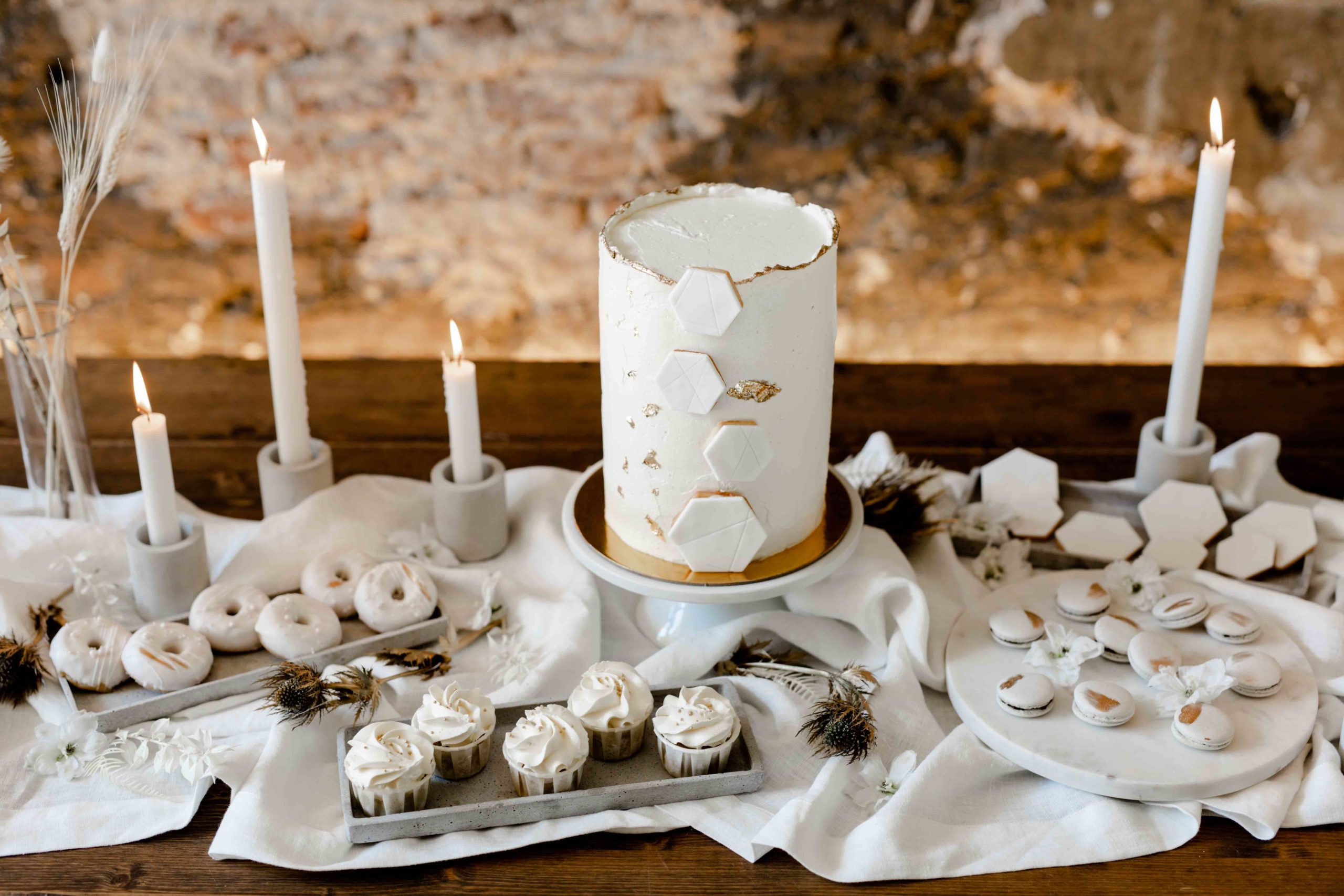 noni Brautmode, Styled Shoot, Tischdekoration für Hochzeit in Weiß mit Kerzenhaltern, weiß-glasierten Mini-Donuts und Trockenblumen und Naked Cake Hochzeitstorte in Weiß