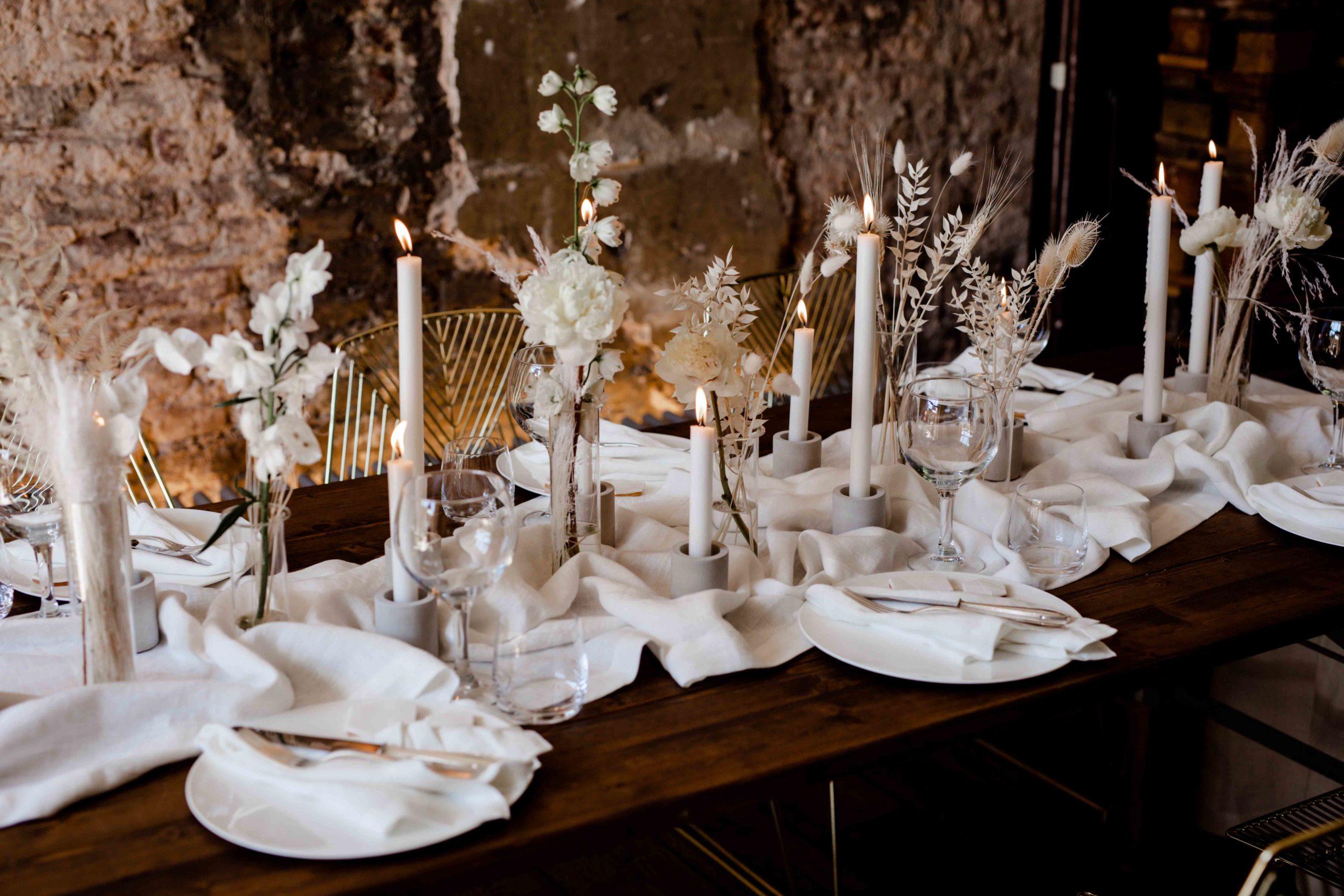 Styled Shoot für Hochzeitsinspiration, Detailaufnahme von Tischdekoration mit Kerzenleuchtern, Tellern und Besteck, Trockenblumen-Gestecken in Weiß, goldenen Chrome-Stühle